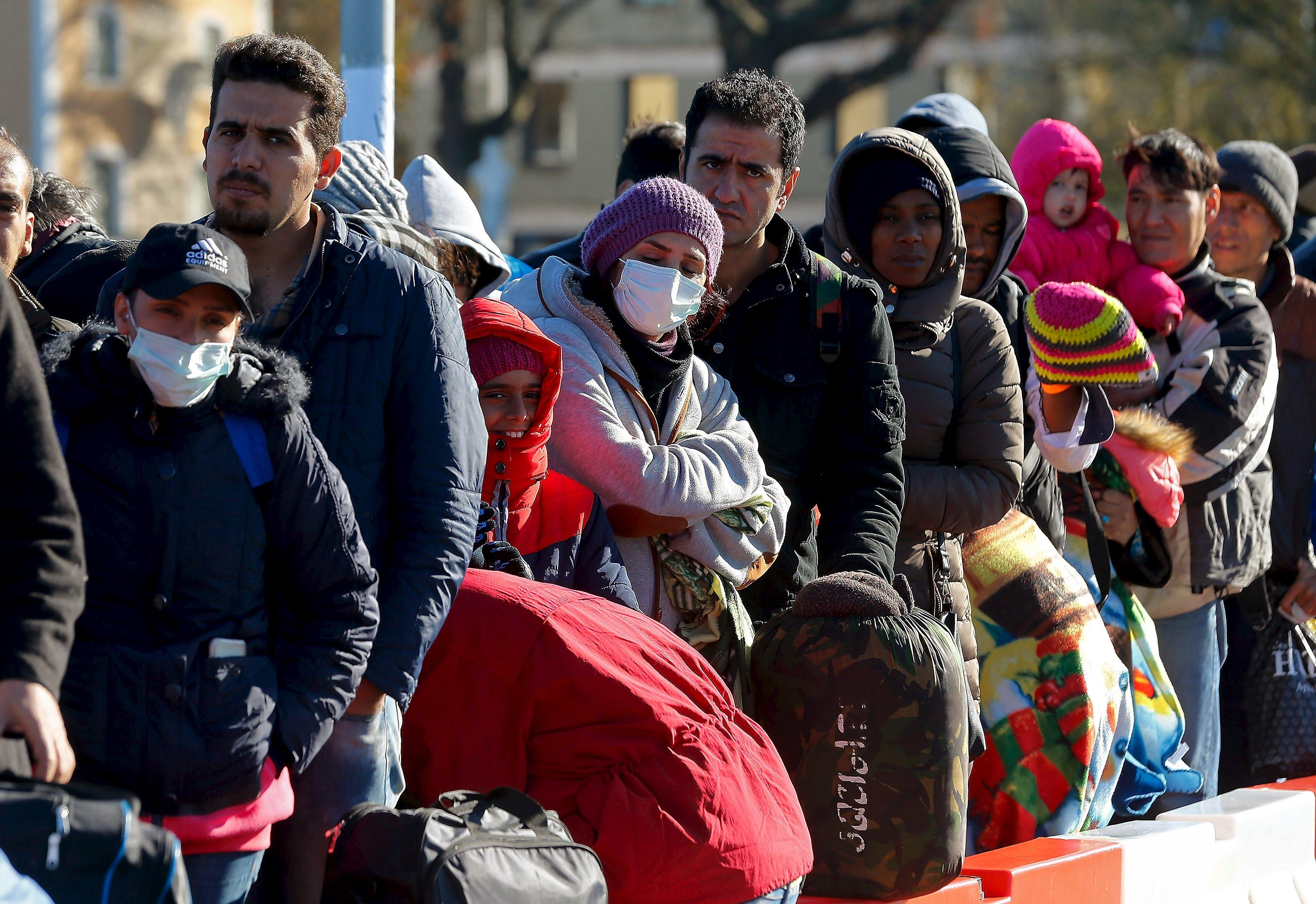 Migrants queue on a bridge crossing the border river Inn at the German-Austrian frontier between Braunau and Simbach am Inn near Passau, Germany November 1, 2015. German Chancellor Angela Merkel failed on Sunday to resolve differences within her ruling coalition on dealing with the crisis over a huge refugee influx, leaving open a row that has dented her conservatives' popularity. REUTERS/Michael Dalder