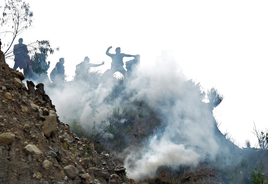 Bolivian coca growers from Los Yungas region confront riot police agents within a tear gas cloud, during a protest against a bill that caps legal coca crops extensions in La Paz on February 21, 2017 (AFP Photo/Aizar RALDES)