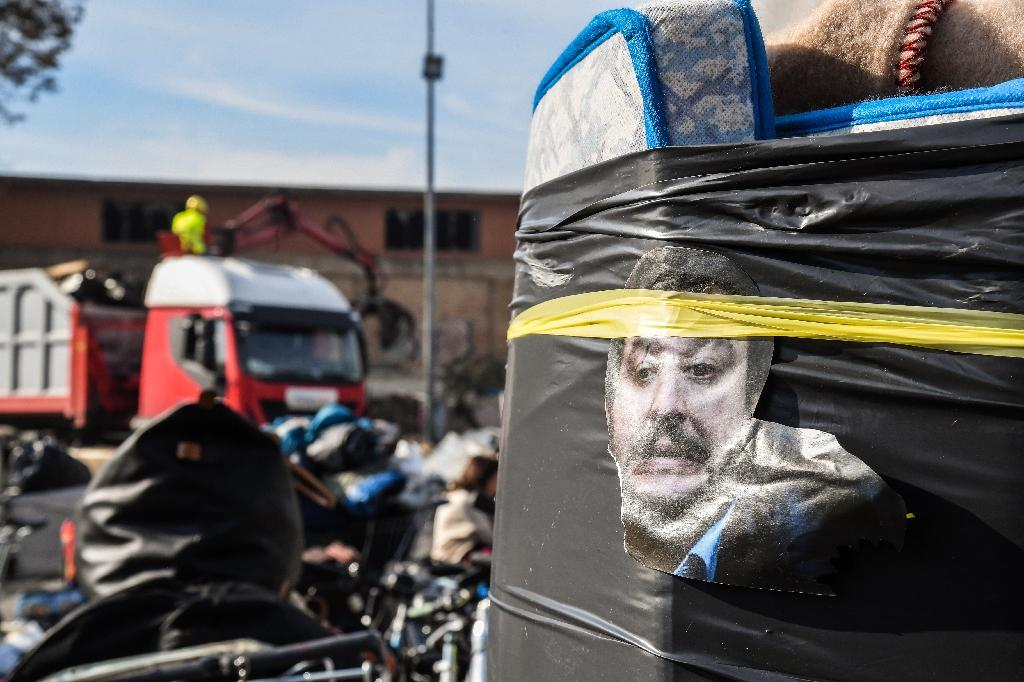 A cutout photo of Italian interior minister Matteo Salvini's head glares from the side of a rolled up mattress as a crane sweeps up discarded belongings at the destruction of a makeshift migrant camp in Rome (AFP Photo/Tiziana FABI)