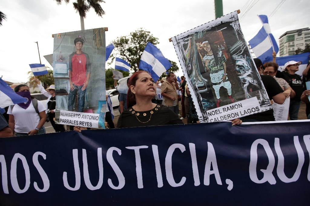 Women who lost their sons in the recent protests hold pictures of their loved ones during a protest demanding justice in Managua (AFP Photo/DIANA ULLOA)