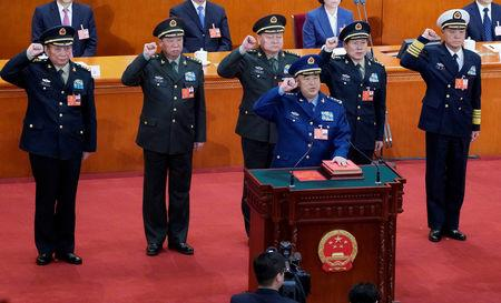 Newly elected vice chairman of the Central Military Commission Xu Qiliang (bottom) and (2nd row L to R) members of the Central Military Commission Zhang Shengmin and Li Zuocheng, vice chairman of the Central Military Commission Zhang Youxia, members of the Central Military Commission Wei Fenghe and Miao Hua, take an oath to the Constitution at the sixth plenary session of the National People's Congress (NPC) at the Great Hall of the People in Beijing, China March 18, 2018. REUTERS/Jason Lee/Files