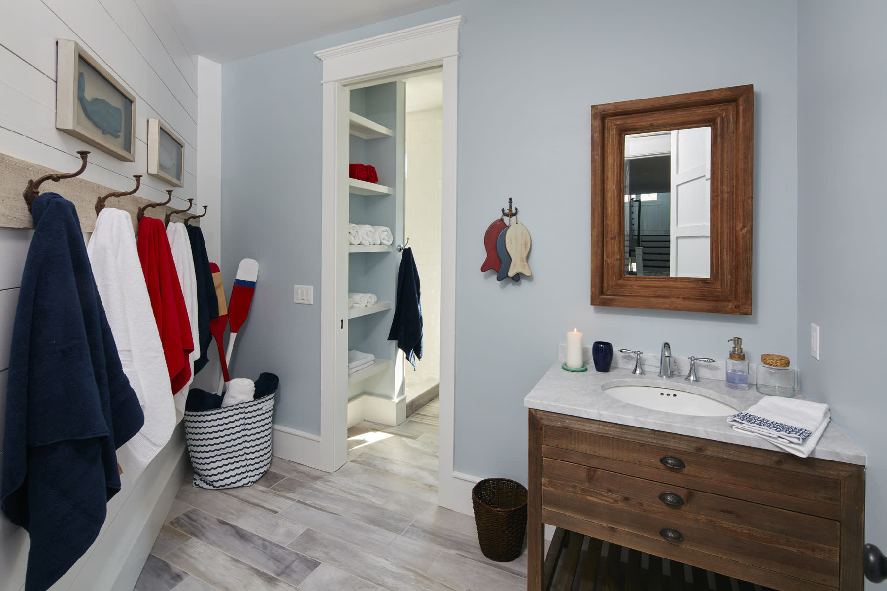 """This photo provided by Marnie Homes shows a bathroom and bedroom area designed by Marnie Oursler. Kids are more likely to place items on shelves, especially if they can drop clothing in baskets, or use hooks rather than hangers to put away their clothing, says designer and builder Oursler, host of the DIY Networks series """"Big Beach Builds."""" (Dana Hoff/Marnie Homes via AP)"""