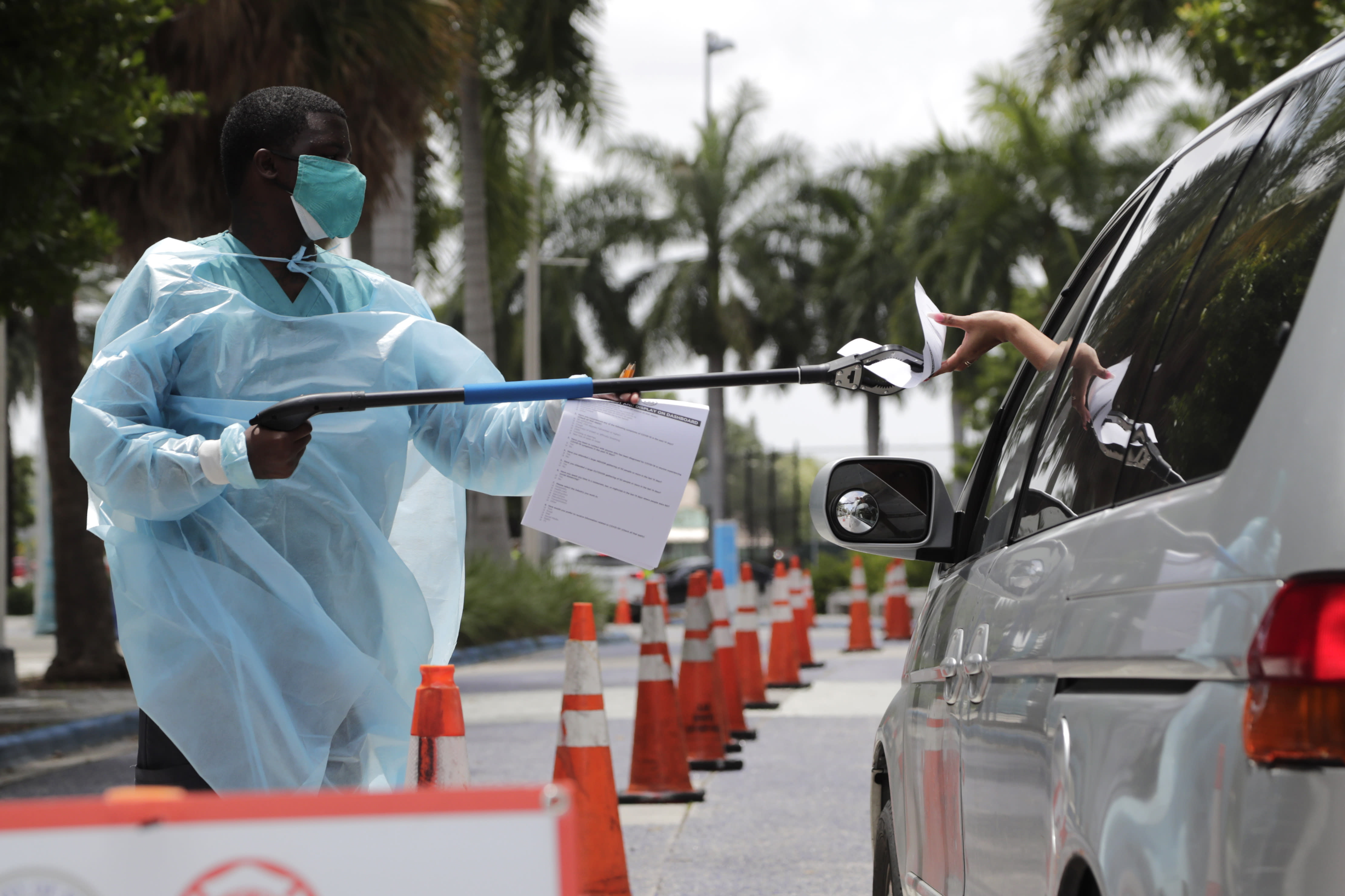 Healthcare worker Dante Hills, left, passes paperwork to a woman in a vehicle at a COVID-19 testing site outside of Marlins Park, Monday, July 27, 2020, in Miami. The Marlins home opener against the Baltimore Orioles on Monday night has been postponed as the Marlins deal with a coronavirus outbreak that stranded them in Philadelphia. (AP Photo/Lynne Sladky)