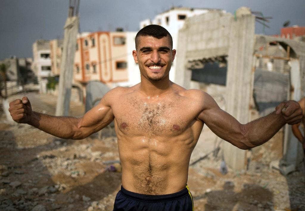 Palestinian Bakr al-Makadmeh, of Bar Palestine group, flexes his muscles during demonstration of a series of exercises, in Gaza City (AFP Photo/Mohammed Abed)