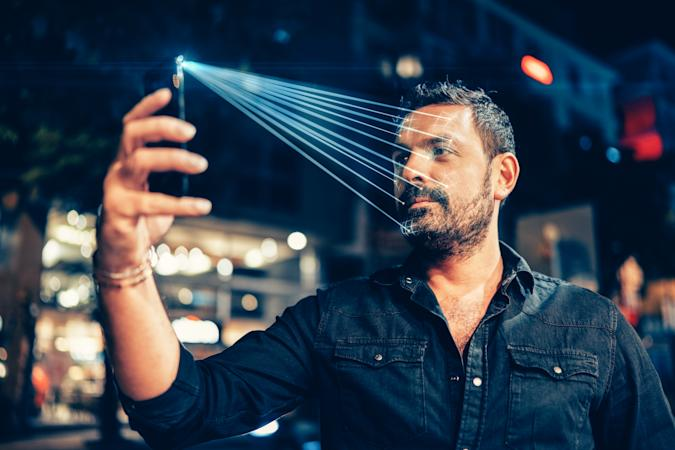 Man using mobile phone for facial recognition.