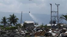 Indonesia using helicopters to spray disinfectant over areas with dead bodies from earthquake and tsunami