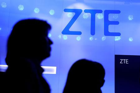FILE PHOTO: People walk past a ZTE logo outside its booth at the Mobile World Congress in Barcelona, Spain, Feb. 25, 2019. REUTERS/Sergio Perez/File Photo