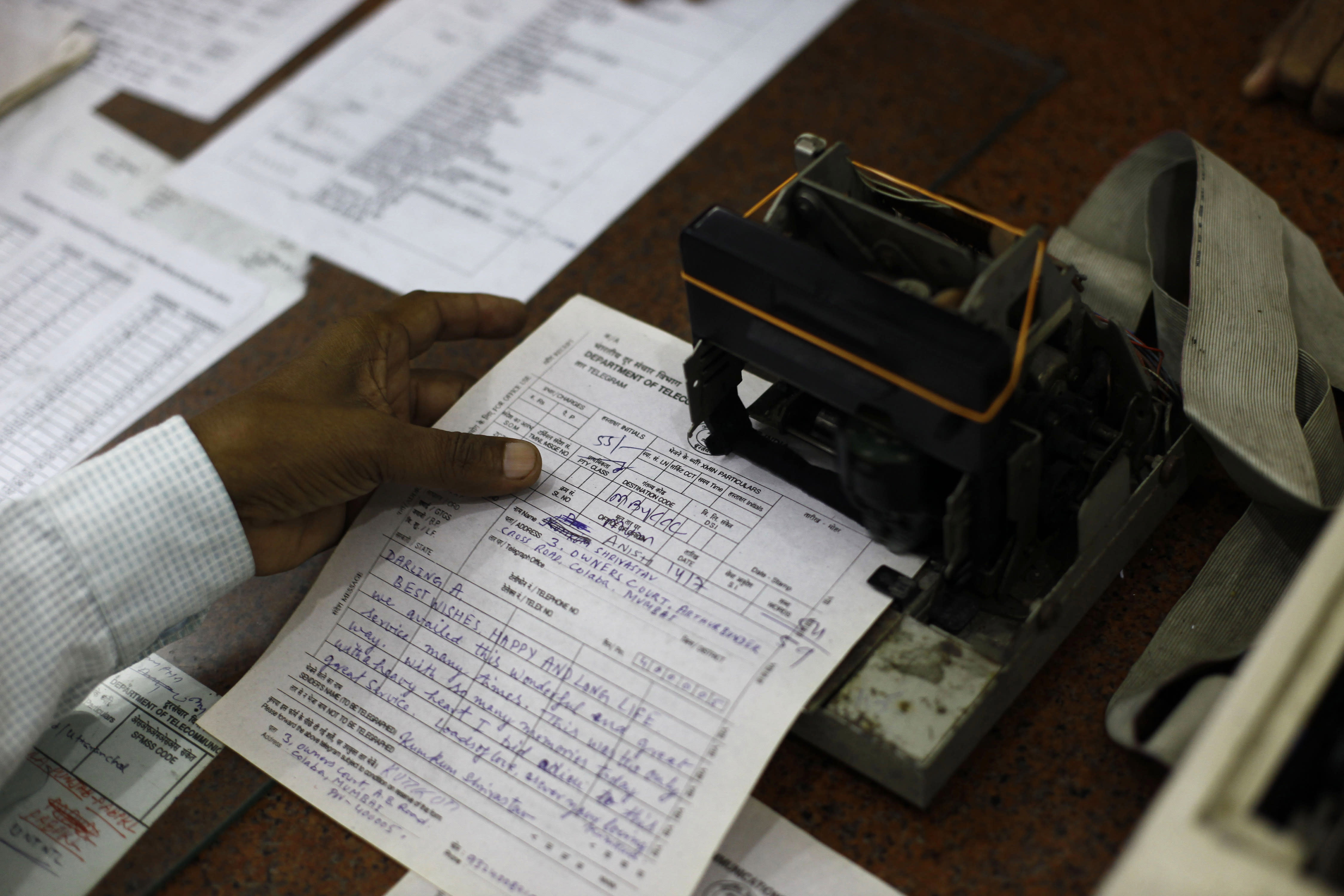 An Indian telegraph employee processes a telegram on the last day of the 163-year-old service at the central telegraph office in Mumbai, India, Sunday, July 14, 2013. Sunday night, the state-run telecommunications company will send its final telegram, closing down a service that fast became a relic in an age of email, reliable landlines and ubiquitous cellphones. (AP Photo/Rafiq Maqbool)