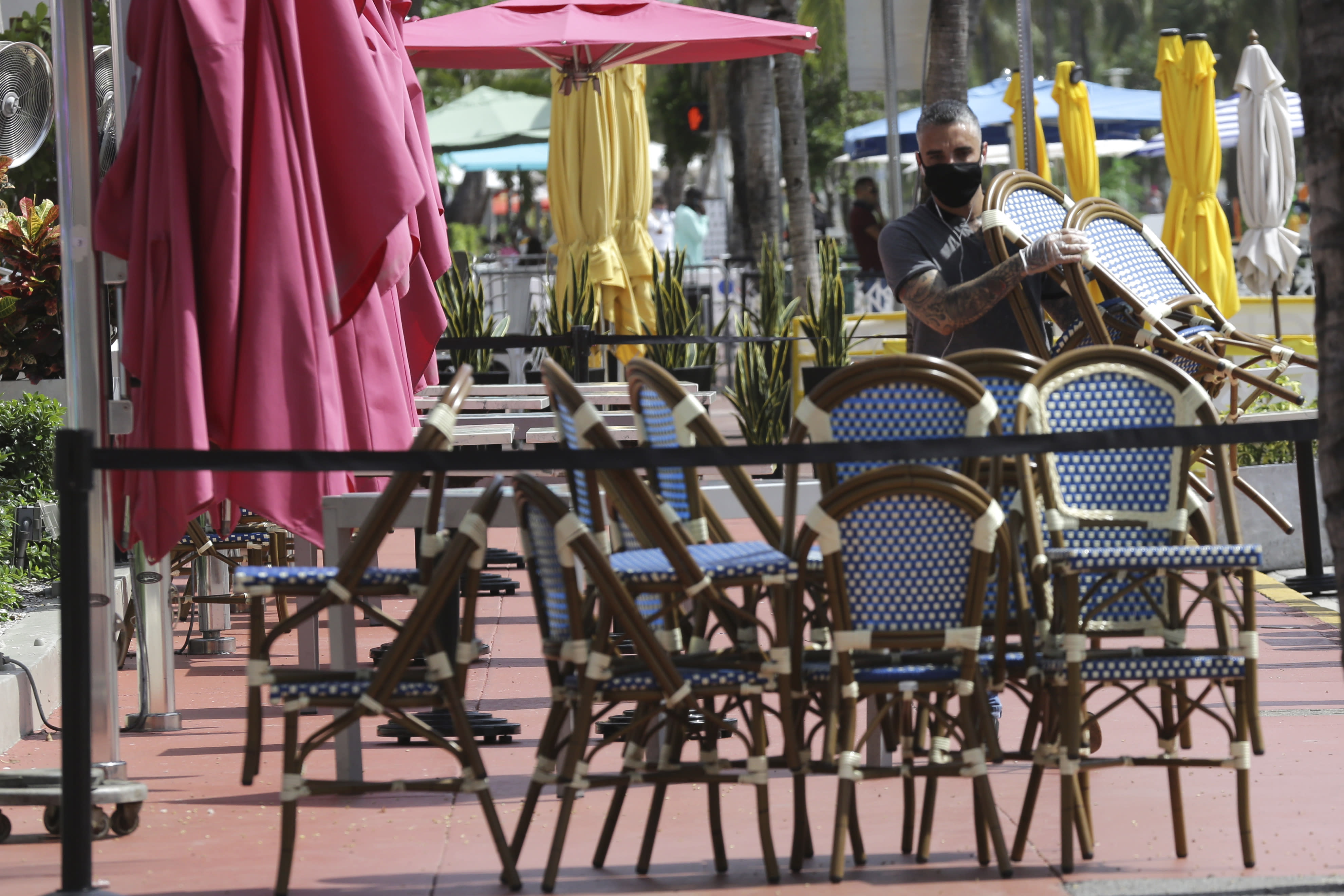 An employee at the Clevelander bar and restaurant on Ocean Drive stacks chairs as they have shut down due to public health concerns caused by COVID-19 during the coronavirus pandemic, Monday, July 13, 2020, in Miami Beach, Fla. (AP Photo/Lynne Sladky)