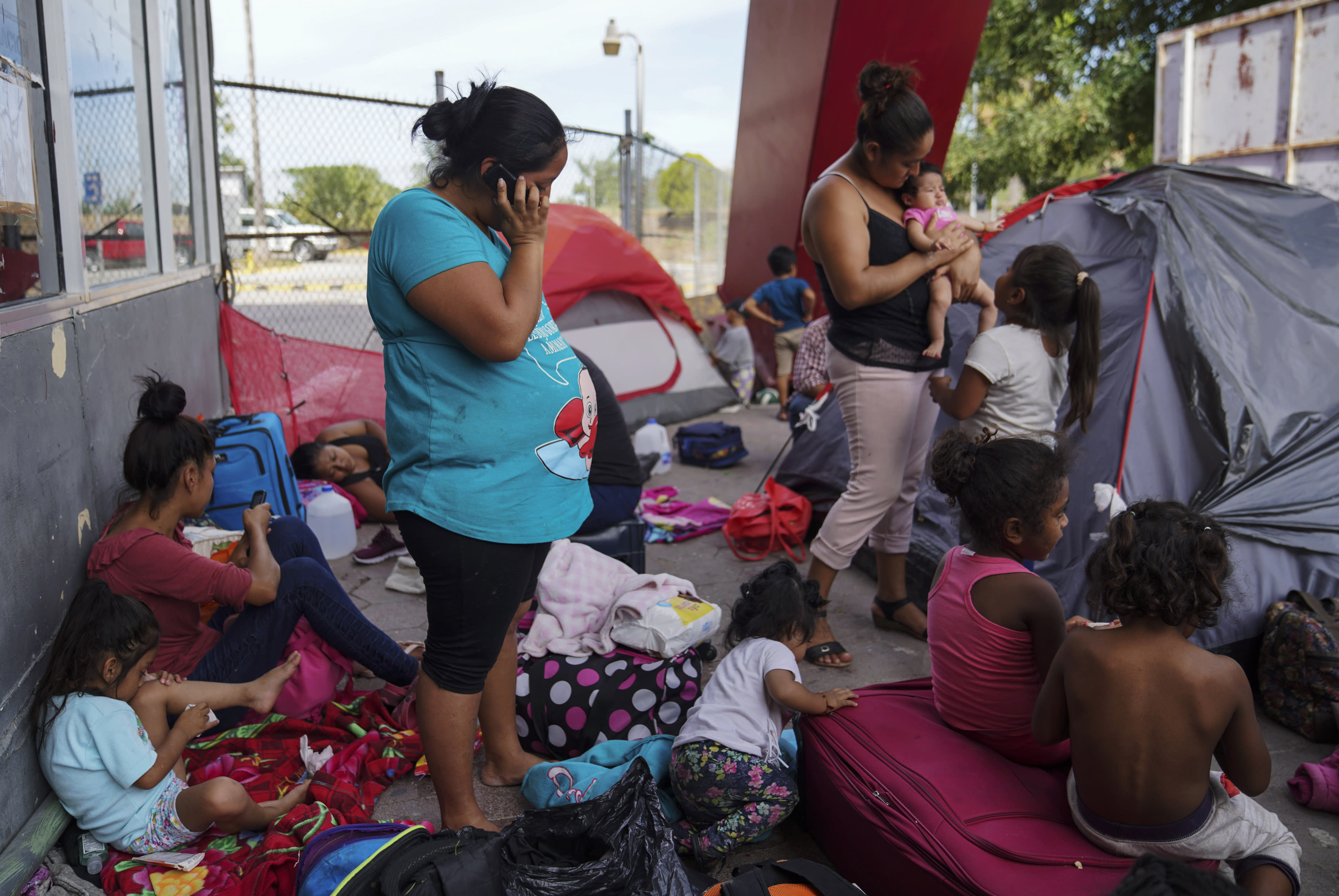In this Aug. 30, 2019, photo, a group of Mexican asylum seekers wait near the Gateway International Bridge in Matamoros, Mexico. Pregnant women face special hazards in Mexico because places where migrants wait to enter the U.S. often don't have access to regular meals, clean water, and medical care. (AP Photo/Veronica G. Cardenas)