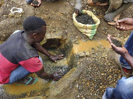 An artisanal miner washes tin ore before it is bagged up and weighed, ready to be transported to the nearest major town for export in the Kalimbi tin mine near the small town of Nyabibwe
