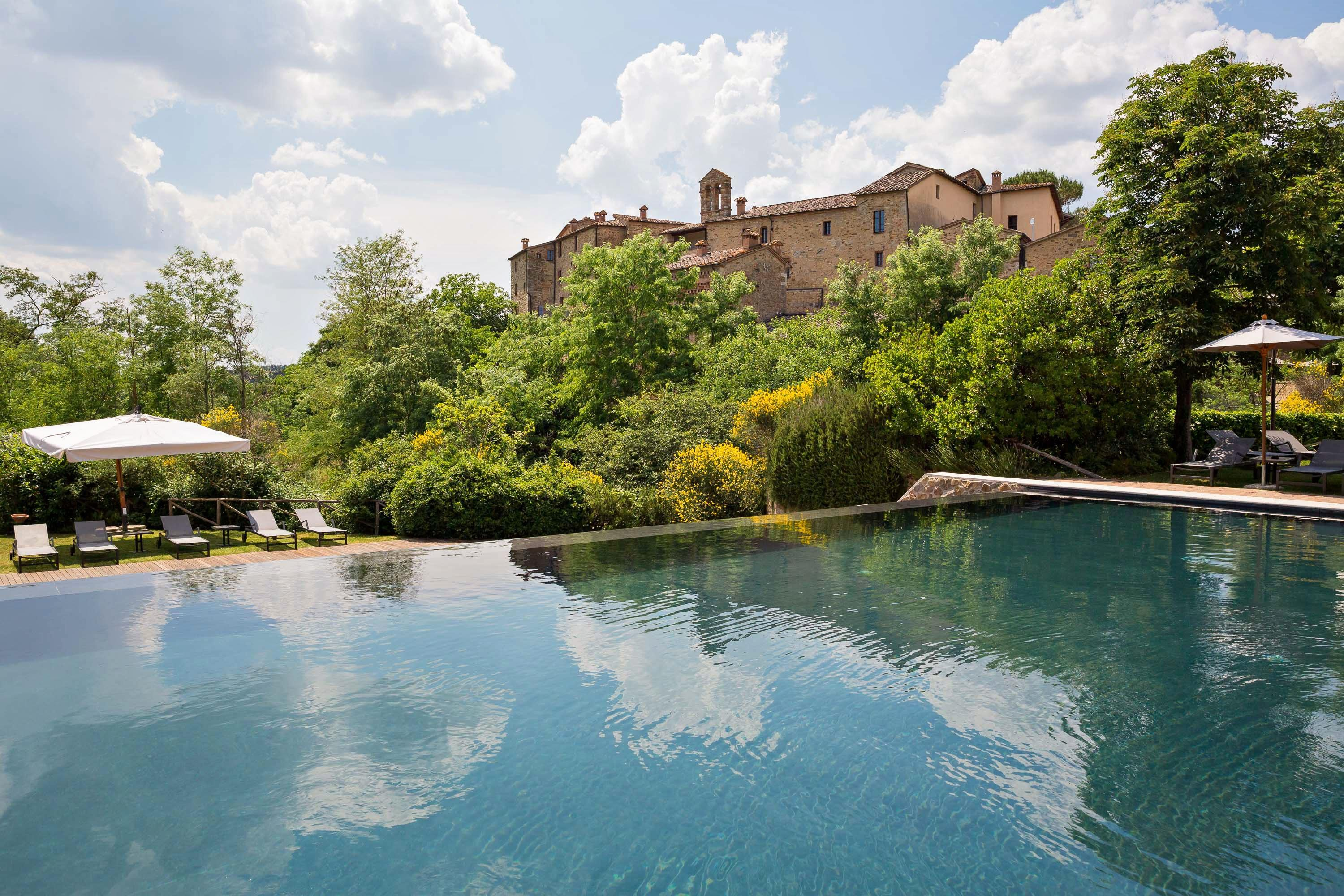 """<a href=""""https://www.castelmonastero.com/"""" rel=""""nofollow noopener"""" target=""""_blank"""" data-ylk=""""slk:A former castle"""" class=""""link rapid-noclick-resp""""><em>A former castle</em></a>: Millennia-old walls and a former monastery and castle now take the form of a stunning design hotel in the heart of Tuscany's Chianti region. A restored medieval village, the luxe retreat has been designed in contemporary Tuscan countryside style. The exclusive design property caters to all tastes with an on-site golf course, a wine bar, gourmet dining, and a fully equipped day spa."""