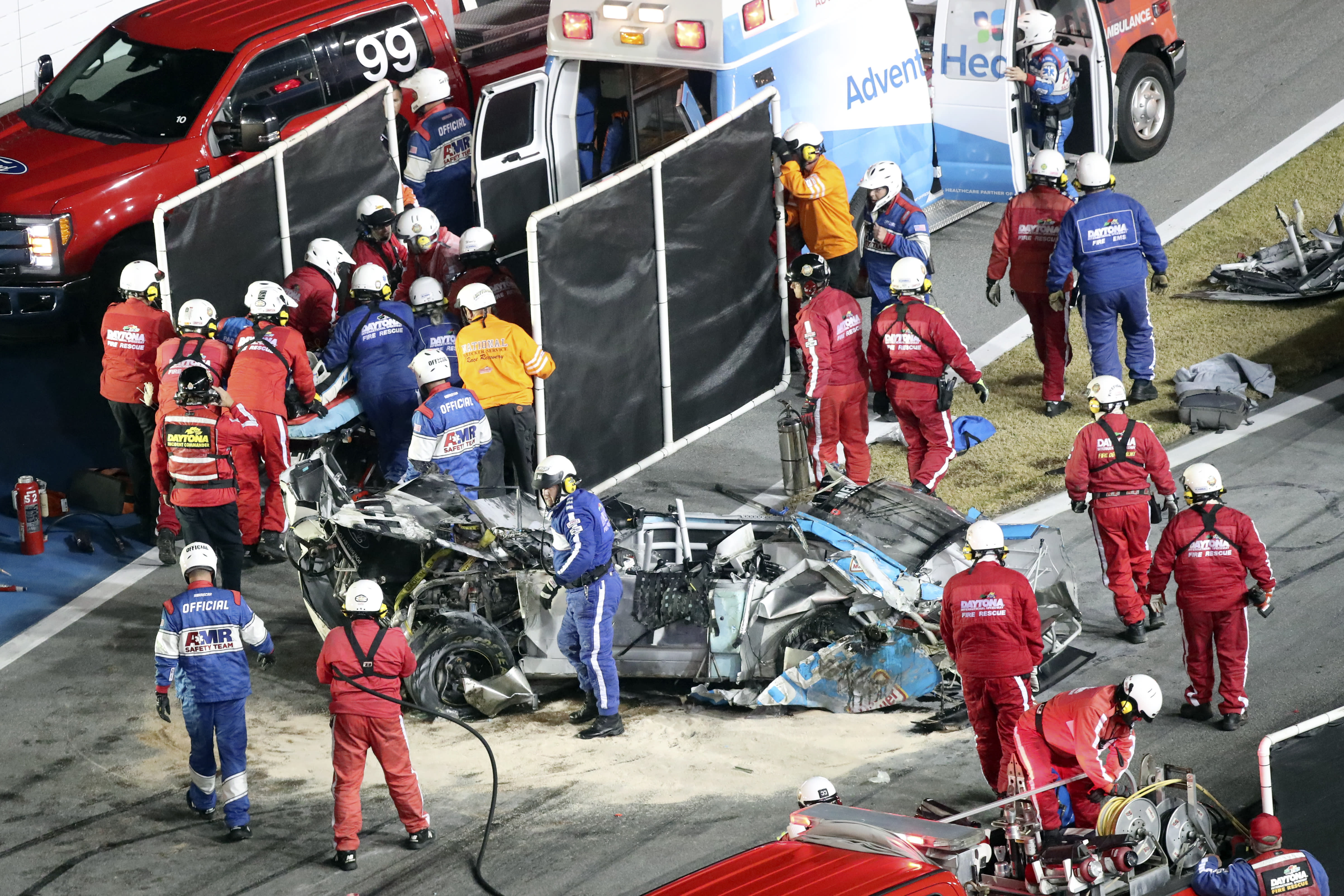 Ryan Newman, left, surrounded by rescue workers is moved to an ambulance after rescue workers removed him from his car after he was involved in a crash on NASCAR Daytona 500 auto race at Daytona International Speedway, Monday, Feb. 17, 2020, in Daytona Beach, Fla. Sunday's race was postponed because of rain. (AP Photo/David Graham)
