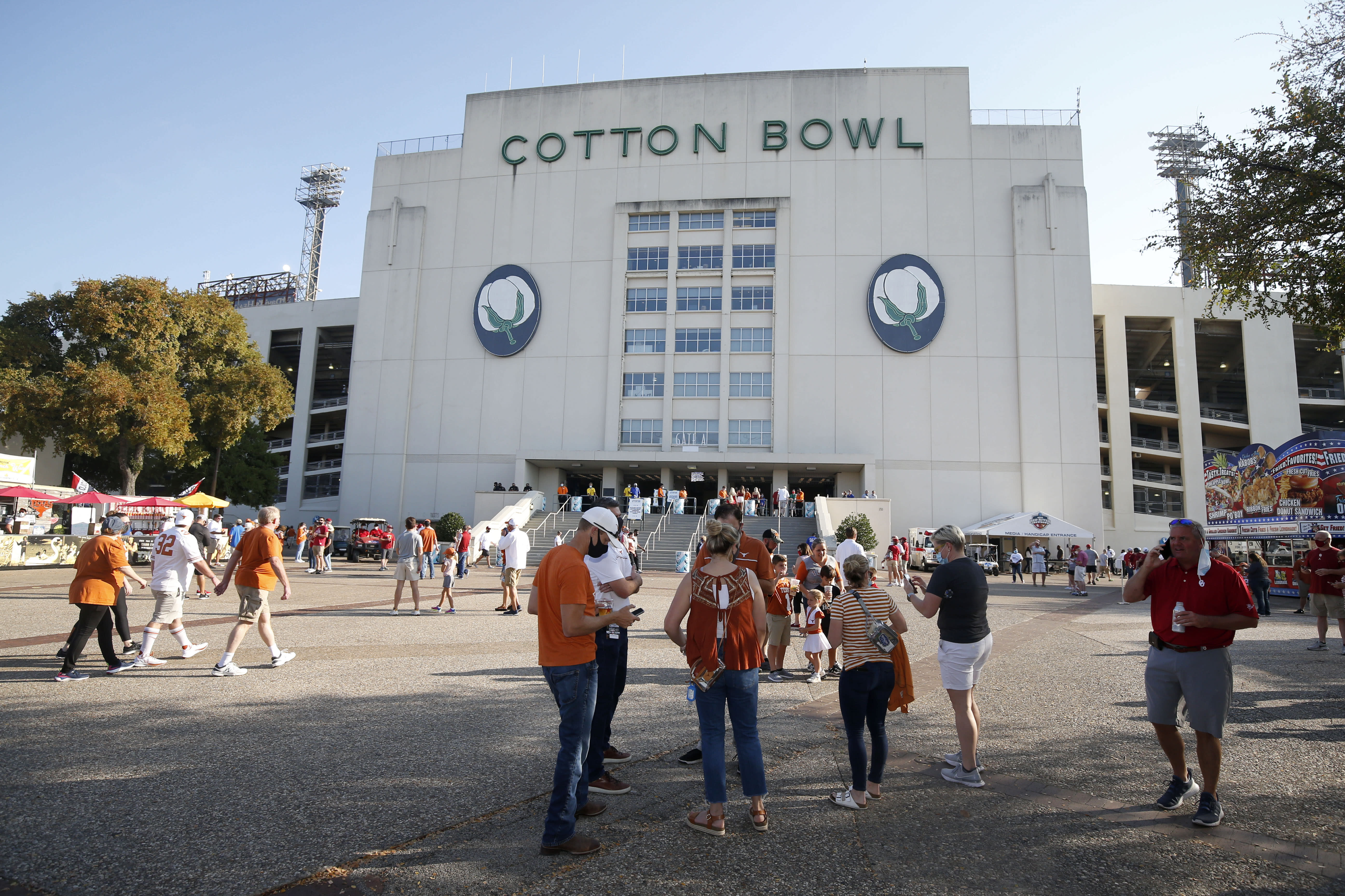 A smaller crowd, due to seating restrictions, mingles outside the Cotton Bowl prior to an NCAA college football game between the University of Texas and Oklahoma, in Dallas Saturday, Oct. 10, 2020. (AP Photo/Michael Ainsworth)