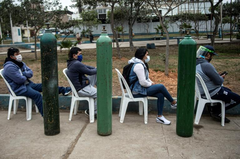 Relatives of COVID-19 patients queue to recharge oxygen cylinders in Peru, which has now passed 400,000 confirmed coronavirus cases (AFP Photo/Ernesto BENAVIDES)