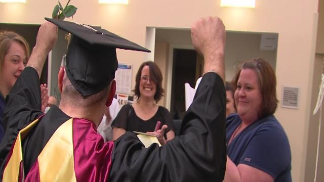 Cancer patient wears his cap and gown to his treatment graduation day