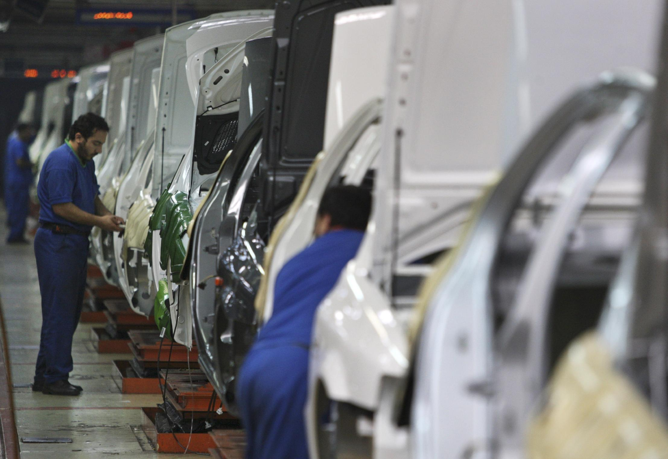 FILE - In this Feb. 7, 2009 file photo, Iranian workers assemble cars at the Iran Khodro automobile manufacturing plant, the biggest car manufacturing company in the Middle East, just outside Tehran, Iran. For many business leaders, Iran is a mouthwatering emerging market, and they could soon find themselves heading to Iran to secure new deals following the suspension of the first international sanctions. (AP Photo/Vahid Salemi, File)
