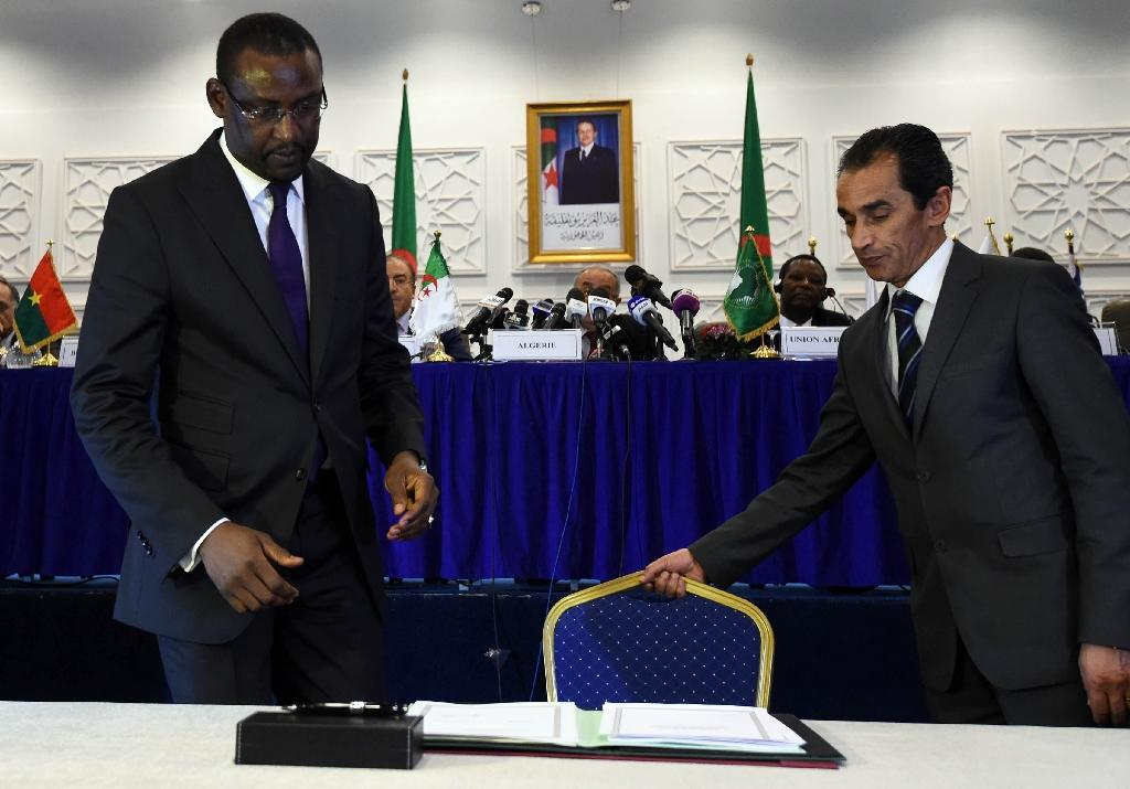 Malian Foreign Minister Abdoulaye Diop (L) prepares to sign a peace agreement as part of mediation talks between the Malian government and some northern armed groups, on March 1, 2015 in Algiers
