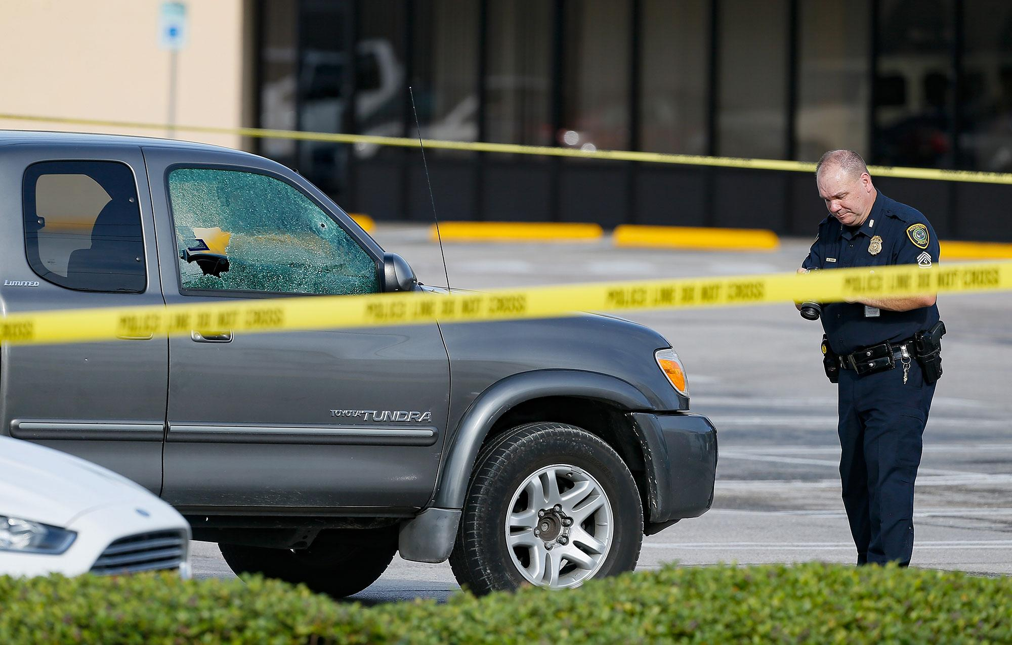 <p>A Houston Police Department investigator photograph a vehicle that received gunshot damage at a scene where nine were wounded in a strip mall shooting on September 26, 2016 in Houston, Texas. (Bob Levey/Getty Images) </p>