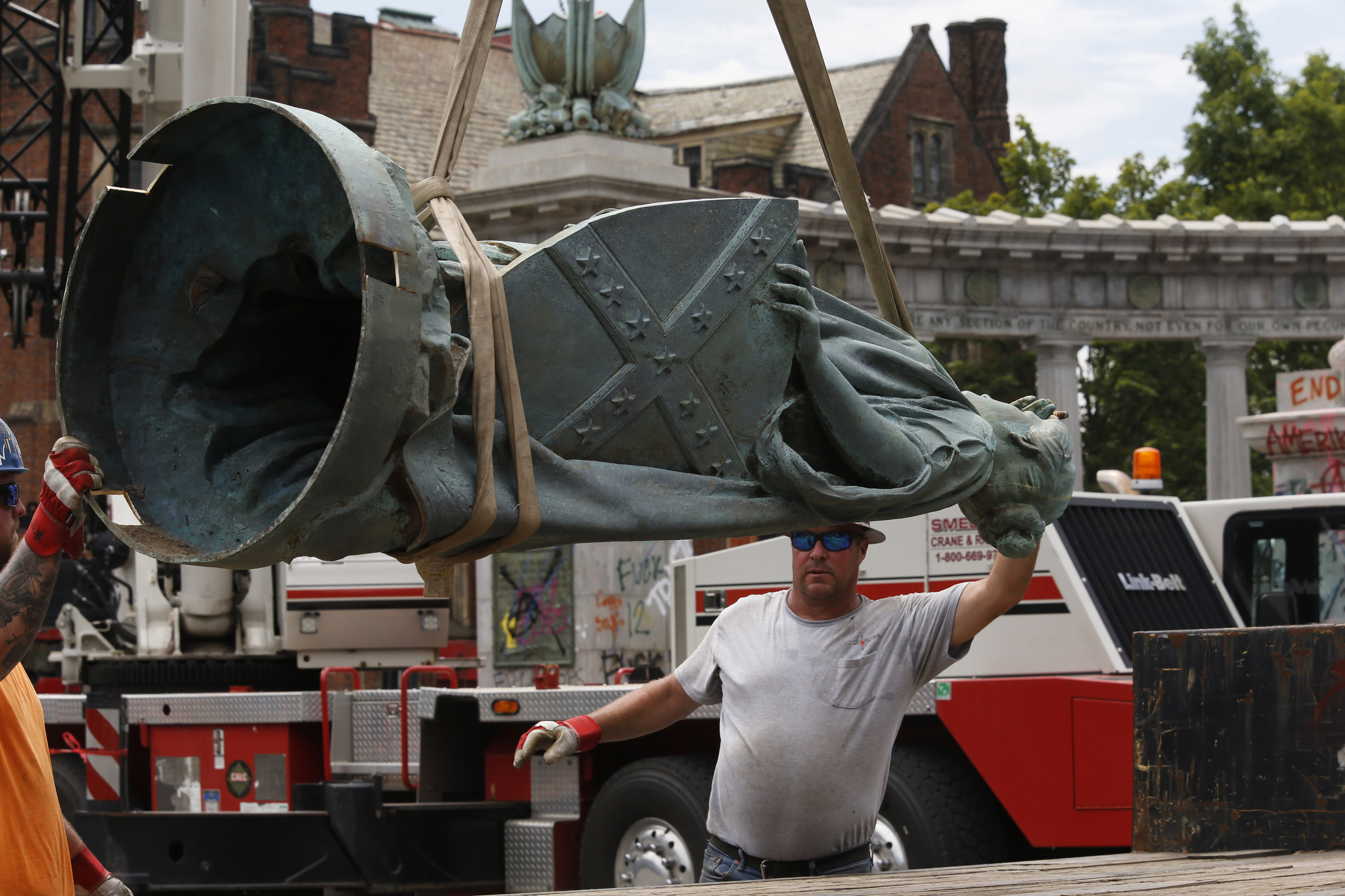 """A workman guides the statue from the Jefferson Davis monument onto a flatbed truck after it was removed from its pedestal on Monument Ave. in Richmond, Va., Wednesday, July 8, 2020. The figure was atop a 65 foot tall Doric column topped by a bronze figure called """"Vindicatrix,"""" also known as """"Miss Confederacy,"""" is the work of Edward Virginius Valentine. (Bob Brown/Richmond Times-Dispatch via AP)"""