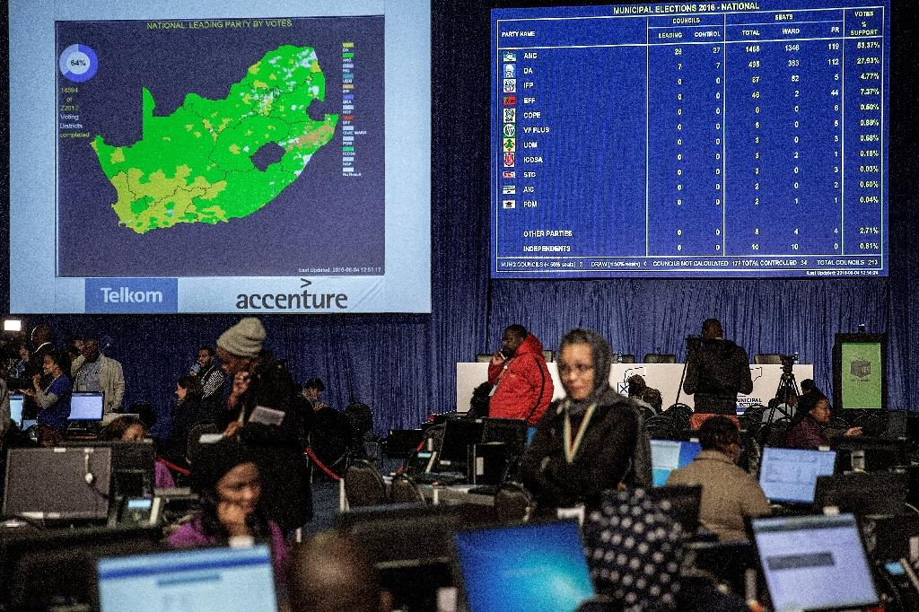 Media personnel, Independent Electoral Commission clerks and officers roam the floor of the Independent Electoral Commission Counting center in Pretoria on August 4, 2016 (AFP Photo/Gianluigi Guercia)