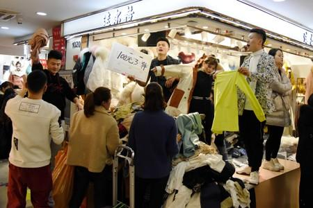 Vendors call out sale discounts to attract consumers at a clothing wholesale market ahead of the Chinese Lunar New Year, in Hangzhou