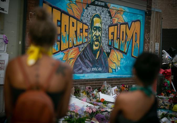 MINNEAPOLIS , MINNESOTA - MAY 31: People defy the curfew to pay their respects at the makeshift memorial and mural outside Cup Foods where George Floyd was murdered by a Minneapolis  police officer on Sunday, May 31, 2020 in Minneapolis , Minnesota. (Jason Armond / Los Angeles Times via Getty Images)