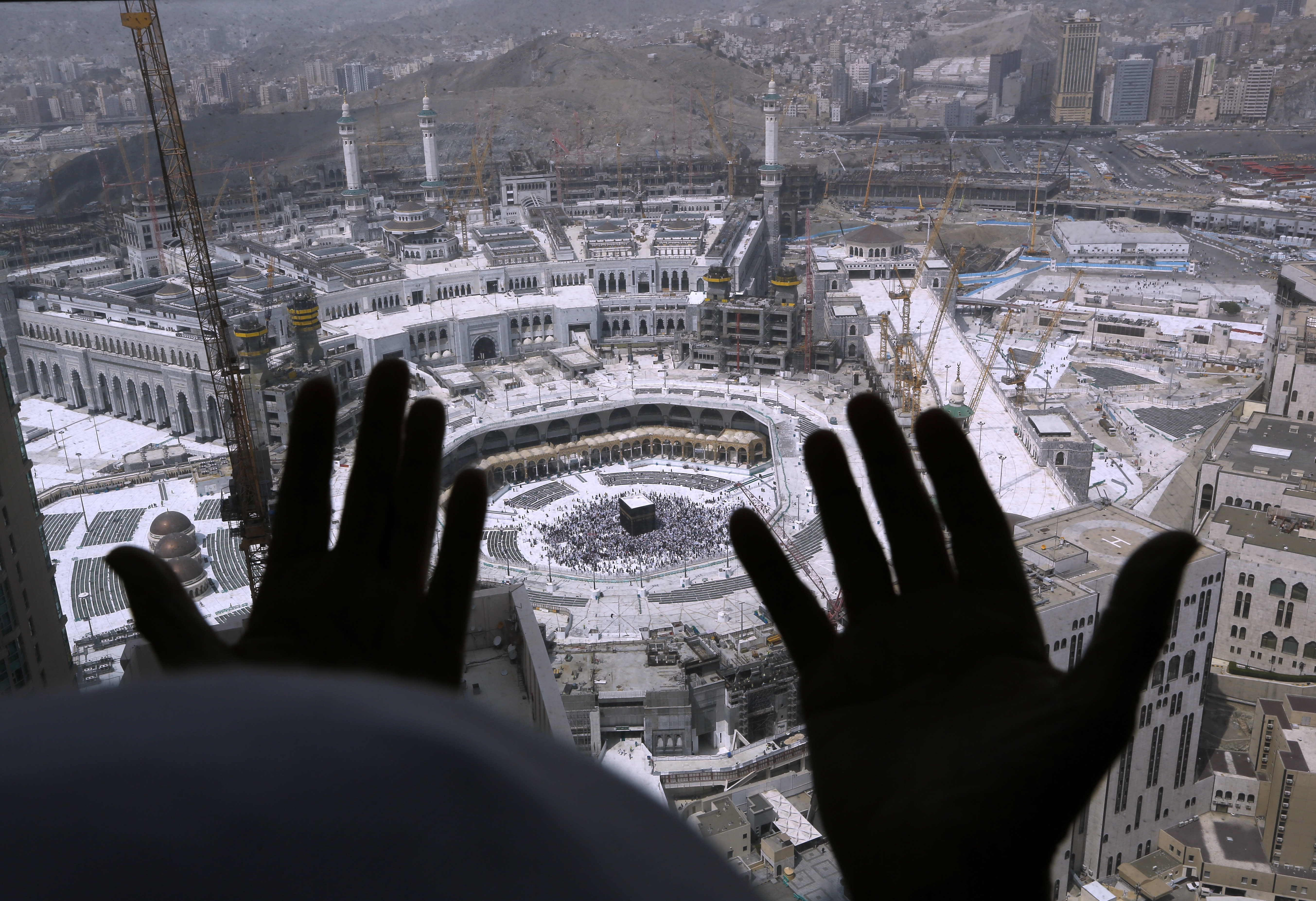 A Muslim prays from a hotel overlooking the Kaaba, the cubic building at the Grand Mosque, in the Muslim holy city of Mecca, Saudi Arabia, Wednesday, March 4, 2020. On Wednesday, Saudi Arabia's Deputy Health Minister Abdel-Fattah Mashat was quoted on the state-linked news site Al-Yaum saying that groups of visitors to Mecca from inside the country would now also be barred from performing the pilgrimage, known as the umrah. (AP Photo/Amr Nabil)