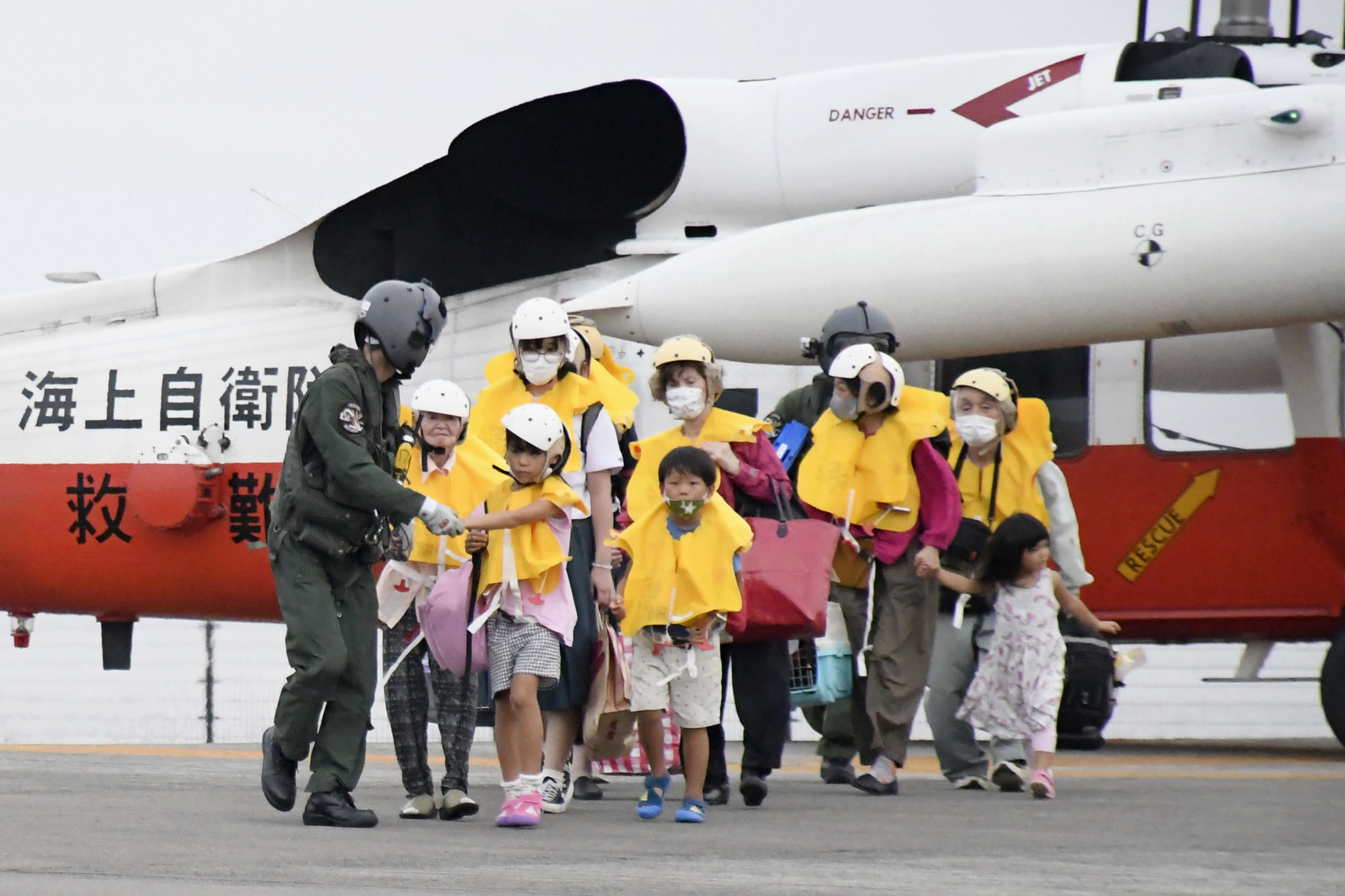 Residents of the islands arrive at a heliport in Kagoshima, southern Japan Friday, Sept. 4, 2020 to take refuge ahead of a powerful typhoon. A powerful typhoon was barreling toward the southern cluster of Japanese Okinawa islands on Saturday, prompting warnings about torrential rainfall and fierce wind gusts. (Kyodo News via AP)