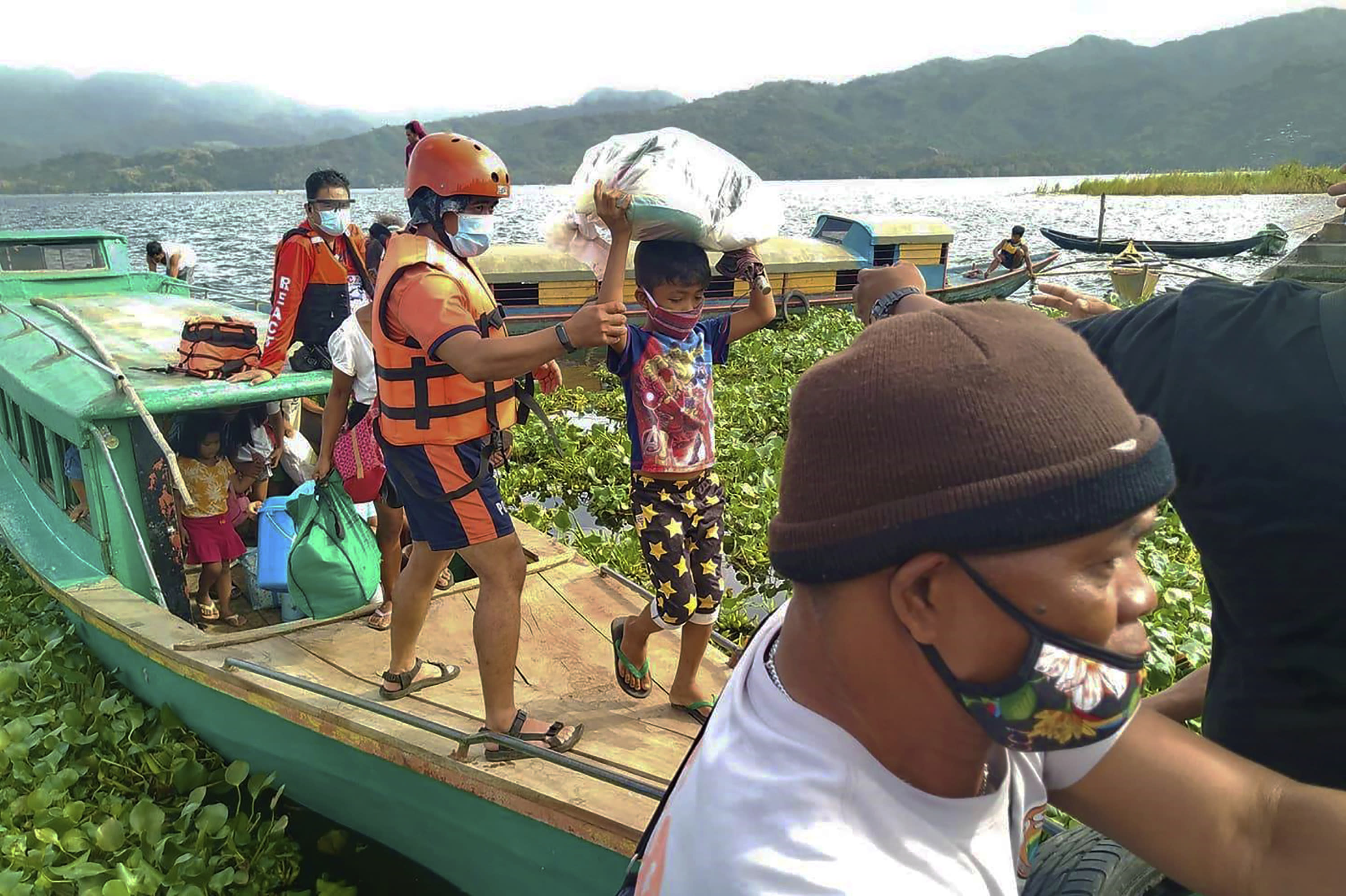 In this photo provided by the Philippine Coast Guard, families are evacuated to safer ground in Camarines Sur province, eastern Philippines on Saturday Oct. 31, 2020 as they prepare for typhoon Goni. Families living near coastal towns have started moving to evacuation centers as the strong typhoon approaches the country. (Philippine Coast Guard via AP)