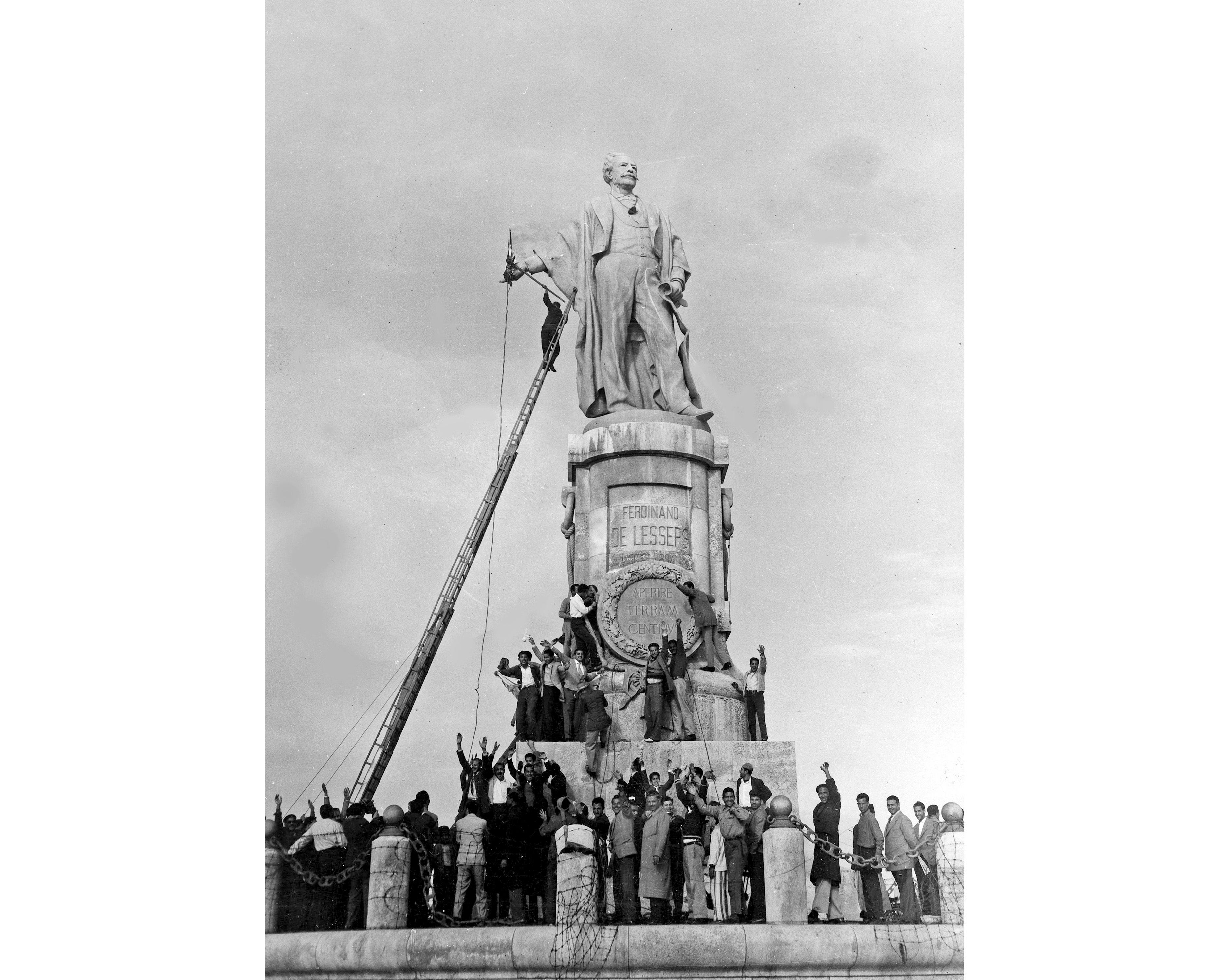 """FILE - In this Dec. 24, 1956 file photo, Egyptian civilians climb on the statue of Ferdinand de Lesseps, the French diplomat who was behind the construction of Egypt's Suez Canal, in Port Said, prior to blowing it up. A proposal to bring back the statue has stirred controversy in Egypt with many saying it would be a salute to colonial times and a """"humiliation"""" to the memory of tens of thousands of Egyptian laborers who died while digging the waterway. The debate started when a newspaper reported in June 2020 that local authorities in the Mediterranean province of Port Said were thinking of returning the statue to where it once stood at the northern entrance of the canal. (AP Photo, File)"""
