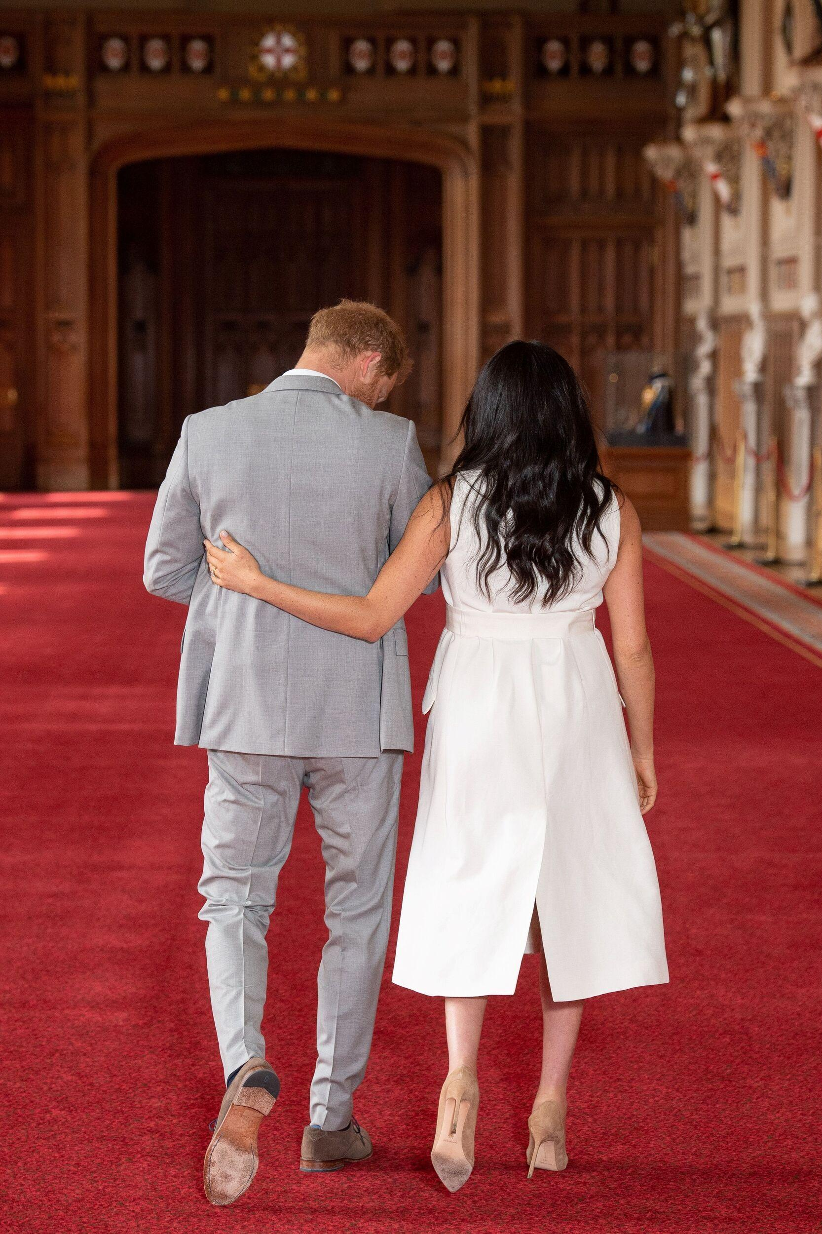 Britain's Prince Harry, Duke of Sussex (L), and his wife Meghan, Duchess of Sussex, walk away after posing for photographs with their newborn baby son in St George's Hall at Windsor Castle in Windsor, west of London on May 8, 2019. (Photo by Dominic Lipinski / POOL / AFP) (Photo credit should read DOMINIC LIPINSKI/AFP/Getty Images)