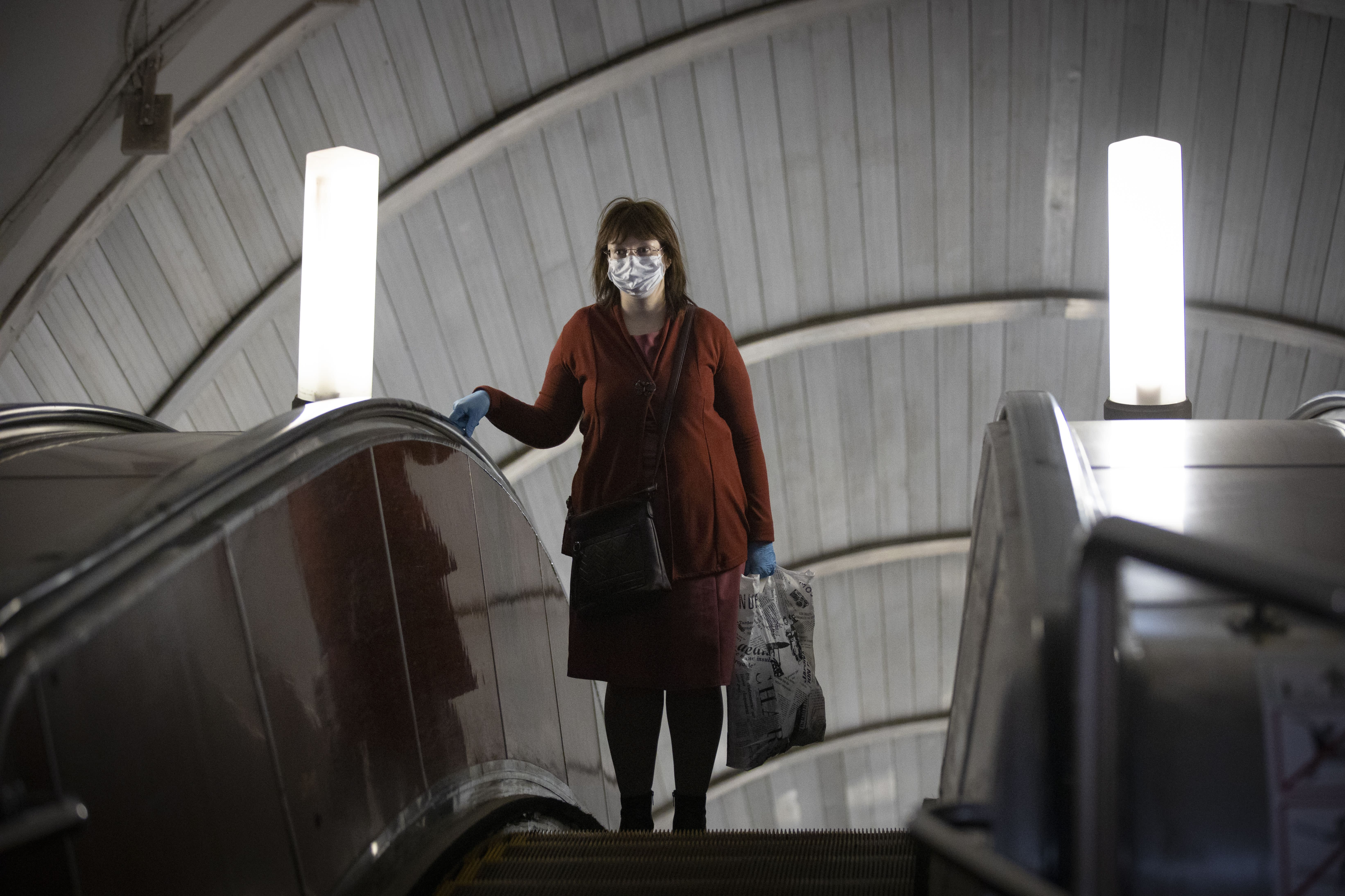 A woman wearing face mask and gloves to protect against coronavirus, observes social distancing guidelines as she travels on the escalator up from the subway in Moscow, Russia, Tuesday, May 12, 2020. From Tuesday onward, wearing face masks and latex gloves is mandatory for people using Moscow's public transport. President Vladimir Putin on Monday declared an end to a partial economic shutdown across Russia due to the coronavirus pandemic, but he said that many restrictions will remain in place. (AP Photo/Alexander Zemlianichenko)