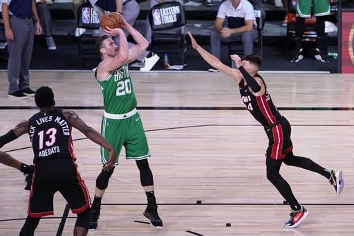 Miami Heat's Bam Adebayo (13) and Tyler Herro, right, defend as Boston Celtics forward Gordon Hayward (20) attempts a shot during the second half of an NBA conference final playoff basketball game, Saturday, Sept. 19, 2020, in Lake Buena Vista, Fla. (AP Photo/Mark J. Terrill)