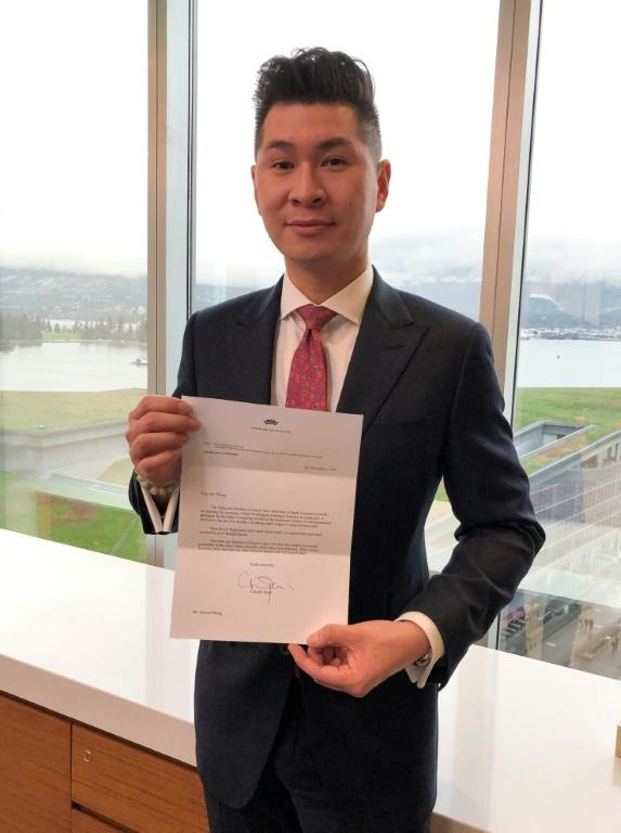 Vancouver lawyer and royal commentator Edward Wang holds a letter from the Duke and Duchess of Sussex thanking him for making a donation to the Jumpstart charity on the occasion of their wedding in 2018 (AFP Photo/Michel COMTE)
