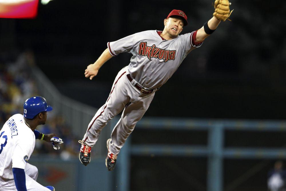 Hanley Ramírez, de los Dodgers de Los Angeles, se roba la segunda base y avanza a tercera mientras Aaron Hill, de los Diamondbacks de Arizona, trata infructuosamente de trapar el tiro desviado del receptor Miguel Montero en el cuarto inning de un partido de las mayores el lunes, 30 de julio del 2012.  (Foto AP/Reed Saxon)
