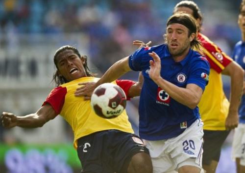 Hugo Pavone (D), de Cruz Azul, lucha por el balón con Joel Huiqui (I) del Morelia, durante un partido del Torneo de Apertura Mexicano en Ciudad de México.