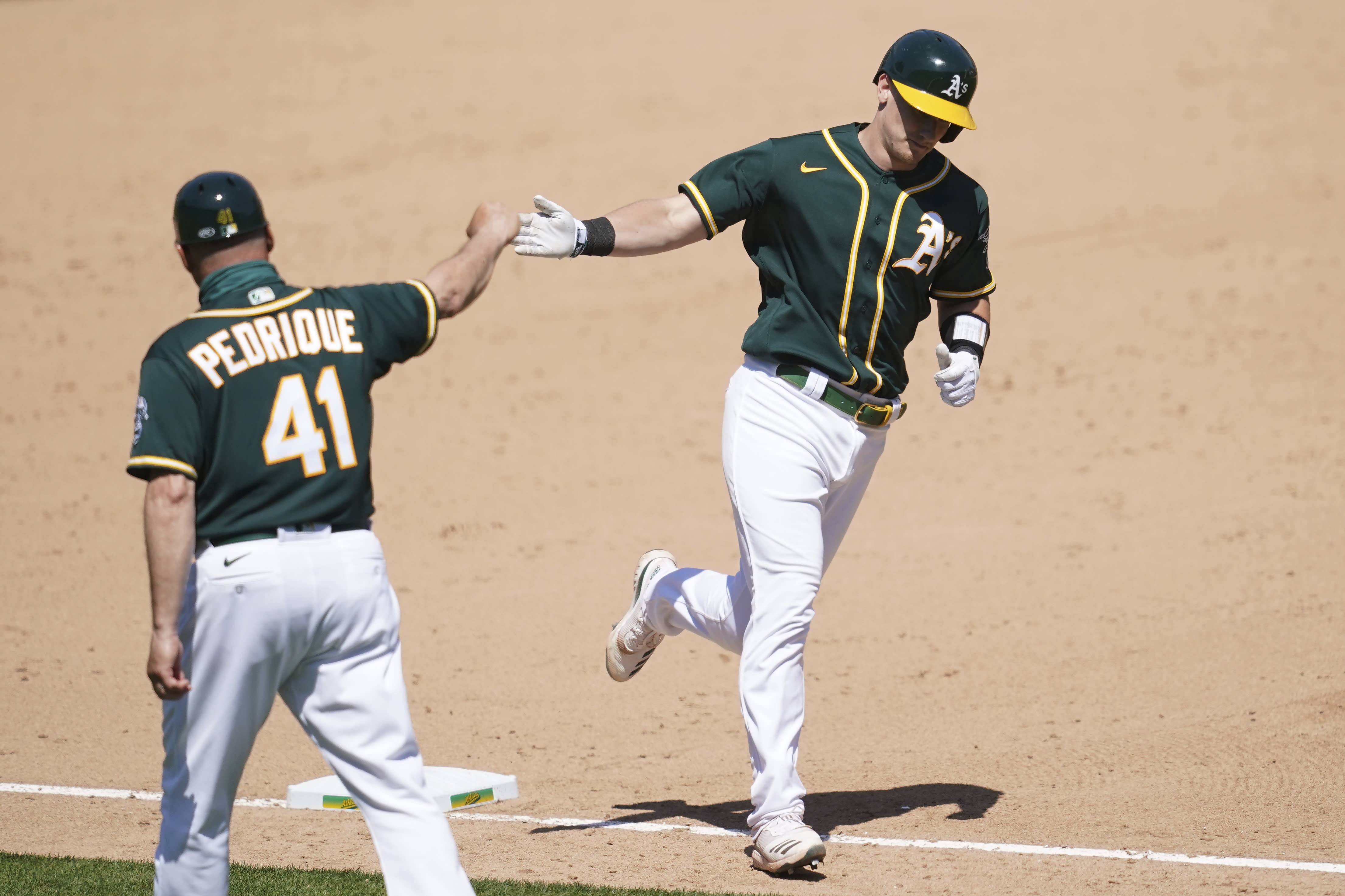 Oakland Athletics' Sean Murphy, right, is congratulated by third base coach Al Pedrique after hitting a solo home run against the Los Angeles Angels during the sixth inning of a baseball game in Oakland, Calif., Sunday, July 26, 2020. (AP Photo/Jeff Chiu)