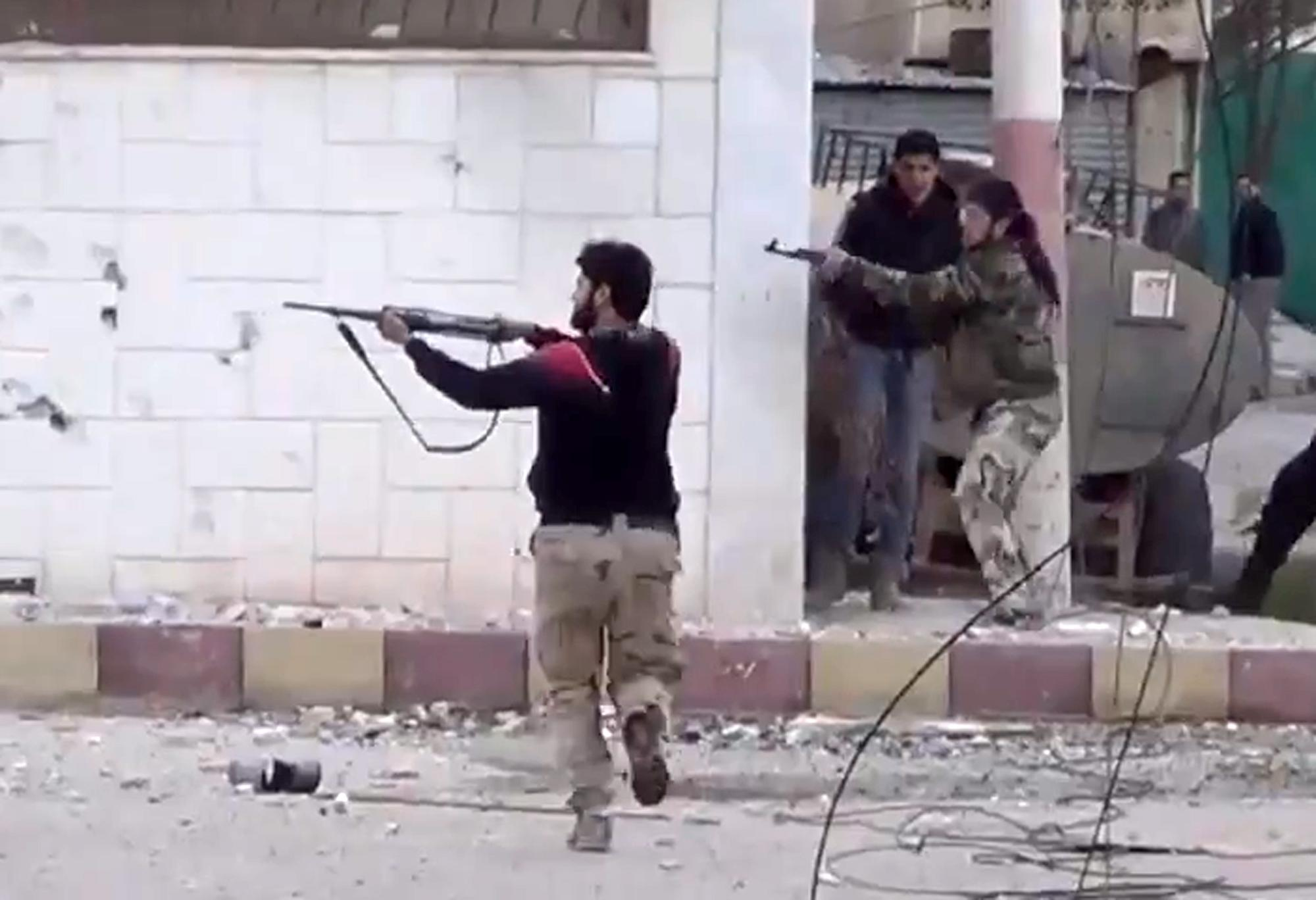FILE - In this Monday March 18, 2013 file image taken from video obtained from the Shaam News Network, which has been authenticated based on its contents and other AP reporting, shows free Syrian Army fighters fire at Syrian army soldiers during a fierce firefight in Daraa al-Balad, Syria. Syrian rebels captured a military base in the south and may be poised to seize control a strategically important region along the border with Jordan, something that would give them a critical gateway to attempt an attack on the capital Damascus. With foreign aid and training of rebels in Jordan ramping up, the opposition fighters have recaptured momentum and may also soon control Syria's side of the Golan Heights along a sensitive border with Israel. (AP Photo/Shaam News Network via AP video, File)
