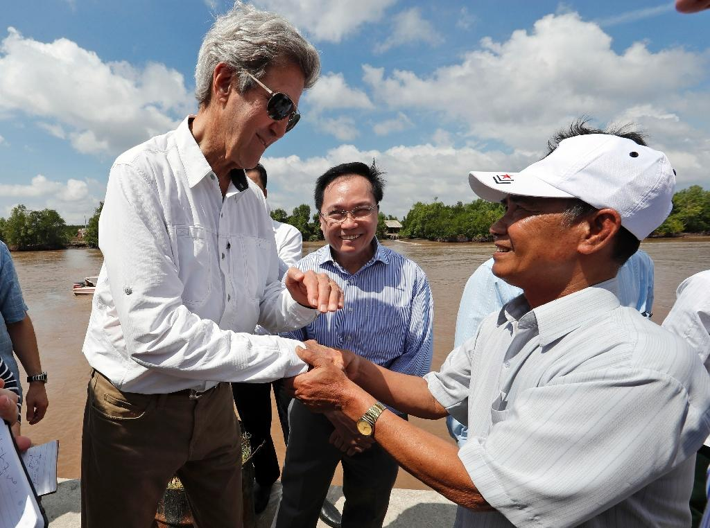 US Secretary of State John Kerry (L) shakes hands with Vo Ban Tam, 70, who was a member of the former Viet Cong guerrilla and who took part in the attack on Kerry's Swift Boat on February 28, 1969 (AFP Photo/Alex Brandon)