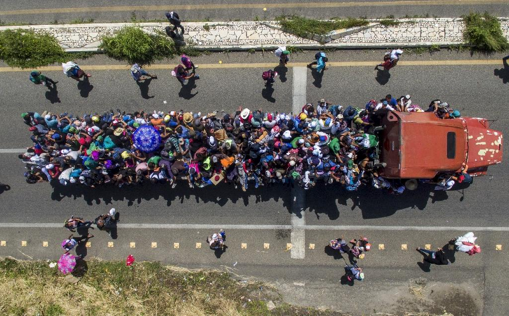 While most migrants have been progressing on foot, some have managed to board buses or trucks to speed their progress. (AFP Photo/PEDRO PARDO)