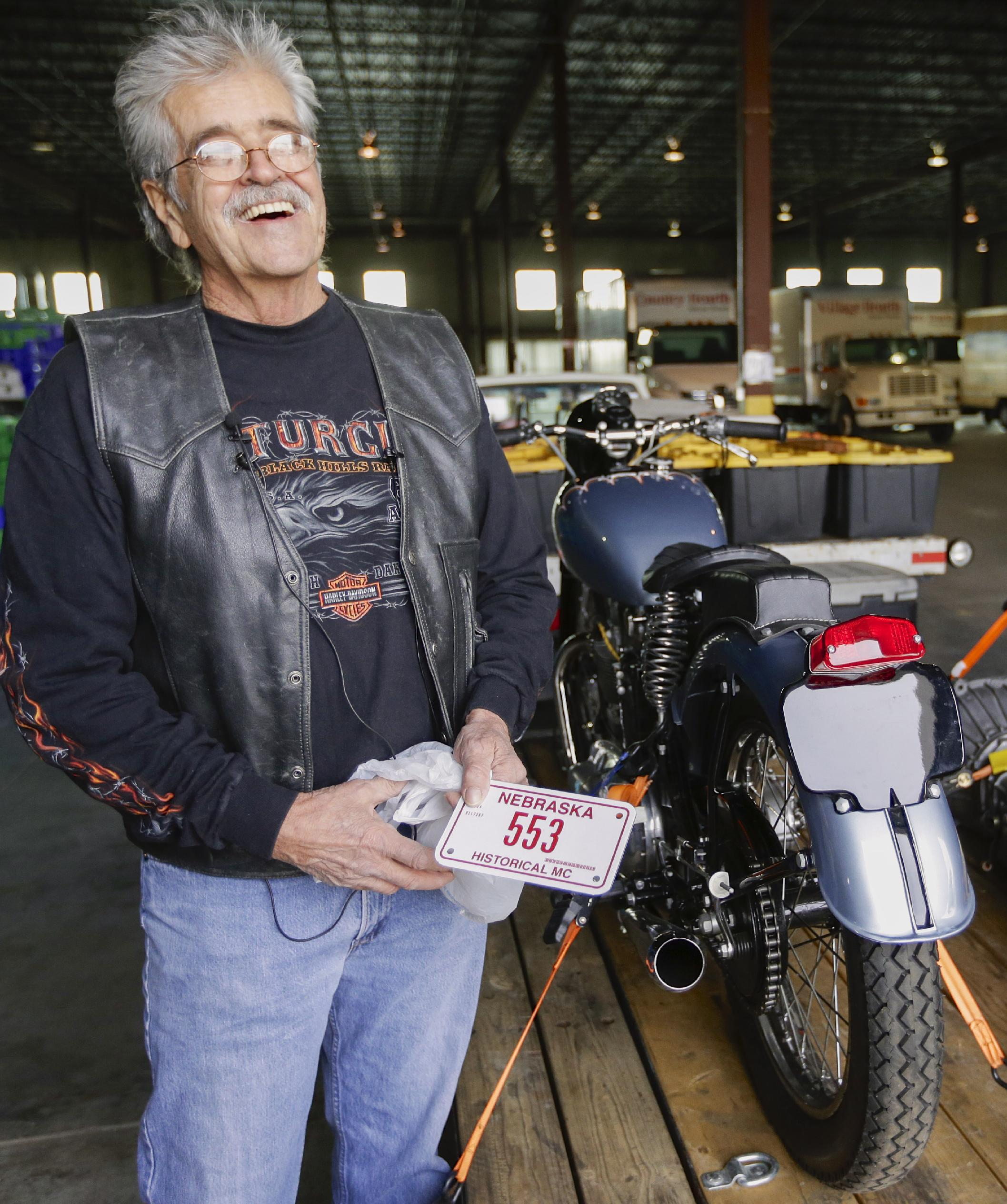 Donald DeVault, 73, smiles before trying to affix a new license plate to his motorcycle in Omaha, Neb., after it was returned to him on Wednesday, Nov. 20, 2013. It was the first time he had seen the bike since it was stolen 46 years ago. California authorities had recovered his 1953 Triumph Tiger 100 at the Port of Los Angeles where it was about to be shipped to Japan. (AP Photo/Nati Harnik)
