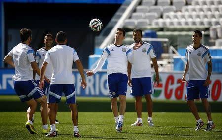 Argentina's Messi controls ball with tem mates during training session at arena di Corinthians stadium in Sao Paulo