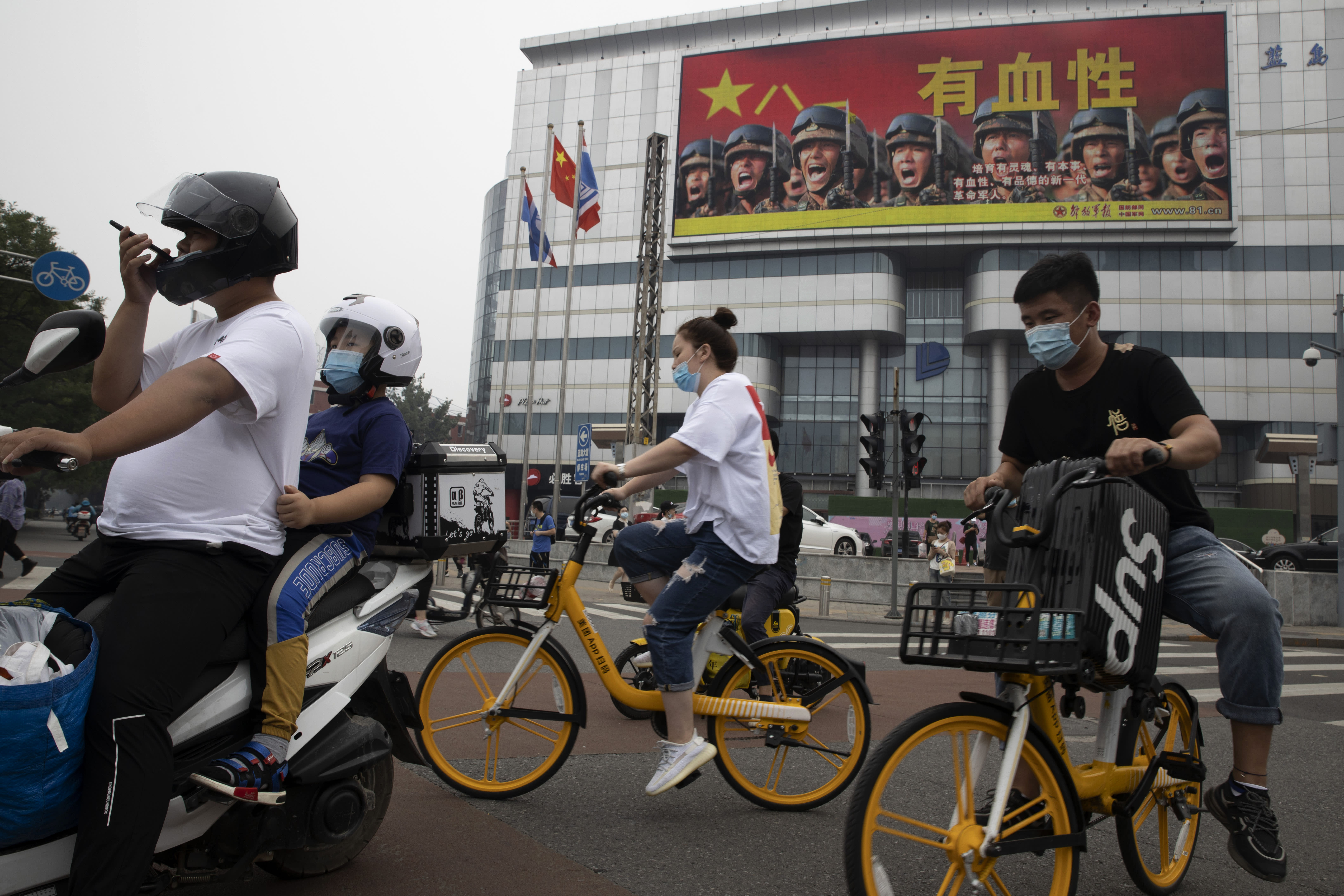"""Residents ride past Chinese military propaganda with the slogan """"Heroic"""" in Beijing on Wednesday, Aug. 26, 2020. China's military test-fired two missiles into the South China Sea, including a """"carrier killer"""" military analysts suggest might have been developed to attack U.S. forces, a newspaper reported Thursday, Aug. 27, 2020. (AP Photo/Ng Han Guan)"""