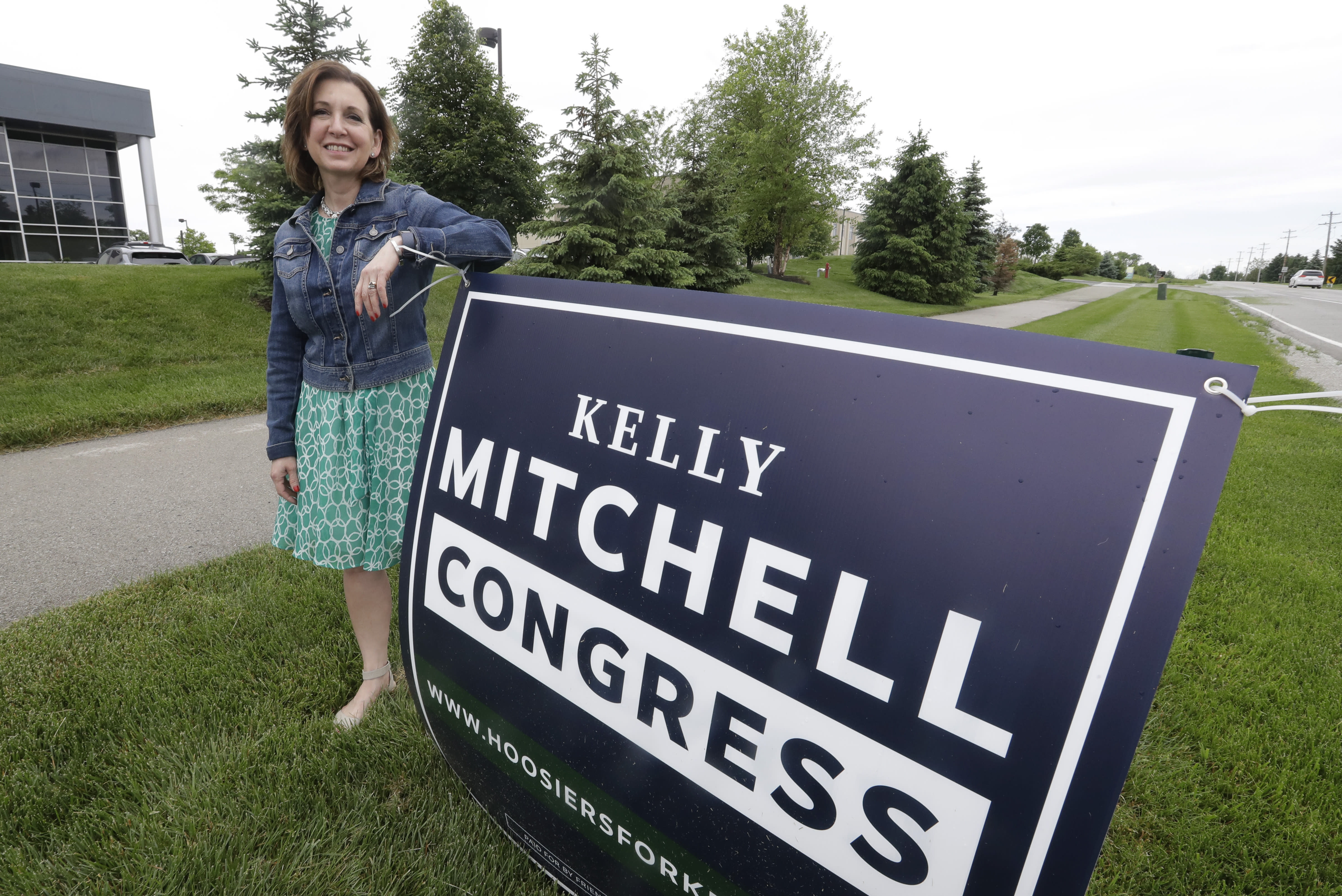 Indiana State Treasurer Kelly Mitchell stands by a campaign sign, Thursday, May 28, 2020, in Westfield, Ind. Mitchell is a candidate for Indiana's 5th Congressional District. More Republican women than ever are seeking House seats this year after the 2018 election further diminished their limited ranks in Congress. But so far it appears that any gains this November could be modest. (AP Photo/Darron Cummings)