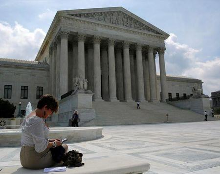 FILE PHOTO: Kristen Luna uses her mobile device at the plaza of the U.S. Supreme Court in Washington