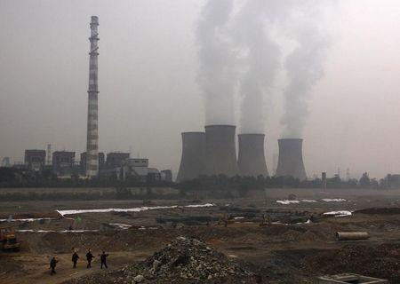 A coal-burning power station can be seen behind migrant workers on the outskirts of Beijing