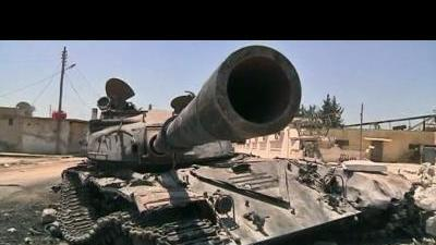 Scorched tanks litter Syrian town