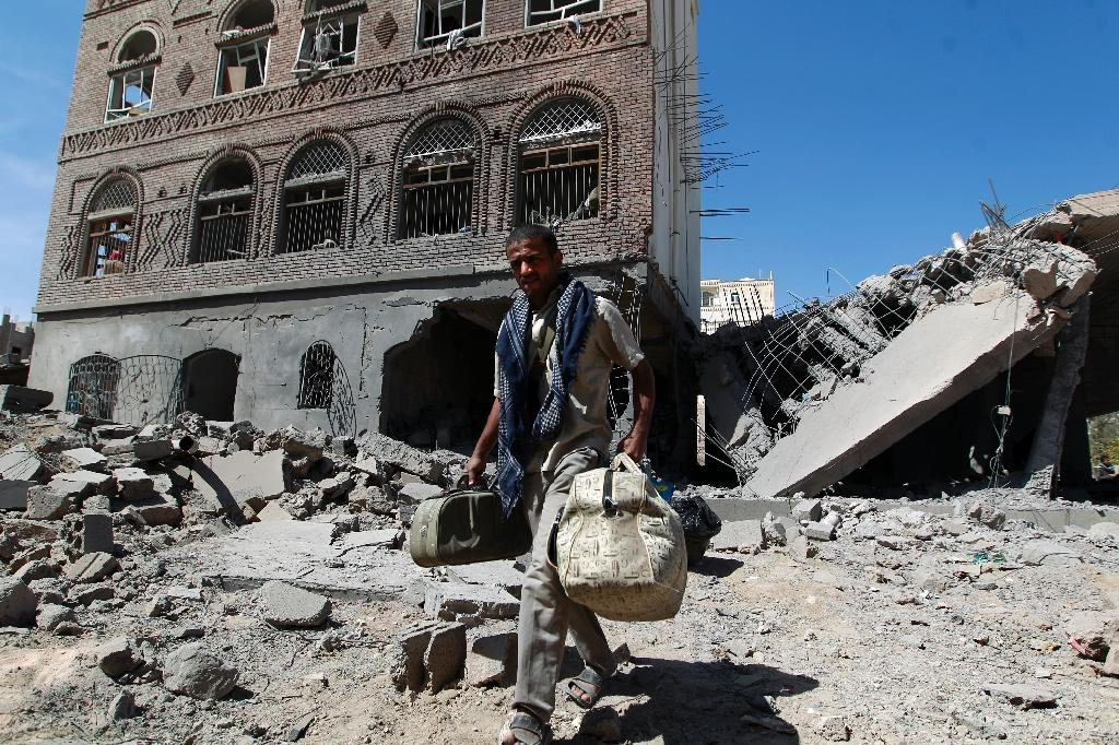 A Yemeni man carries his bags through the ruins of buildings destroyed in an air-strike by the Saudi-led coalition in the capital Sanaa on October 28, 2015 (AFP Photo/Mohammed Huwais)