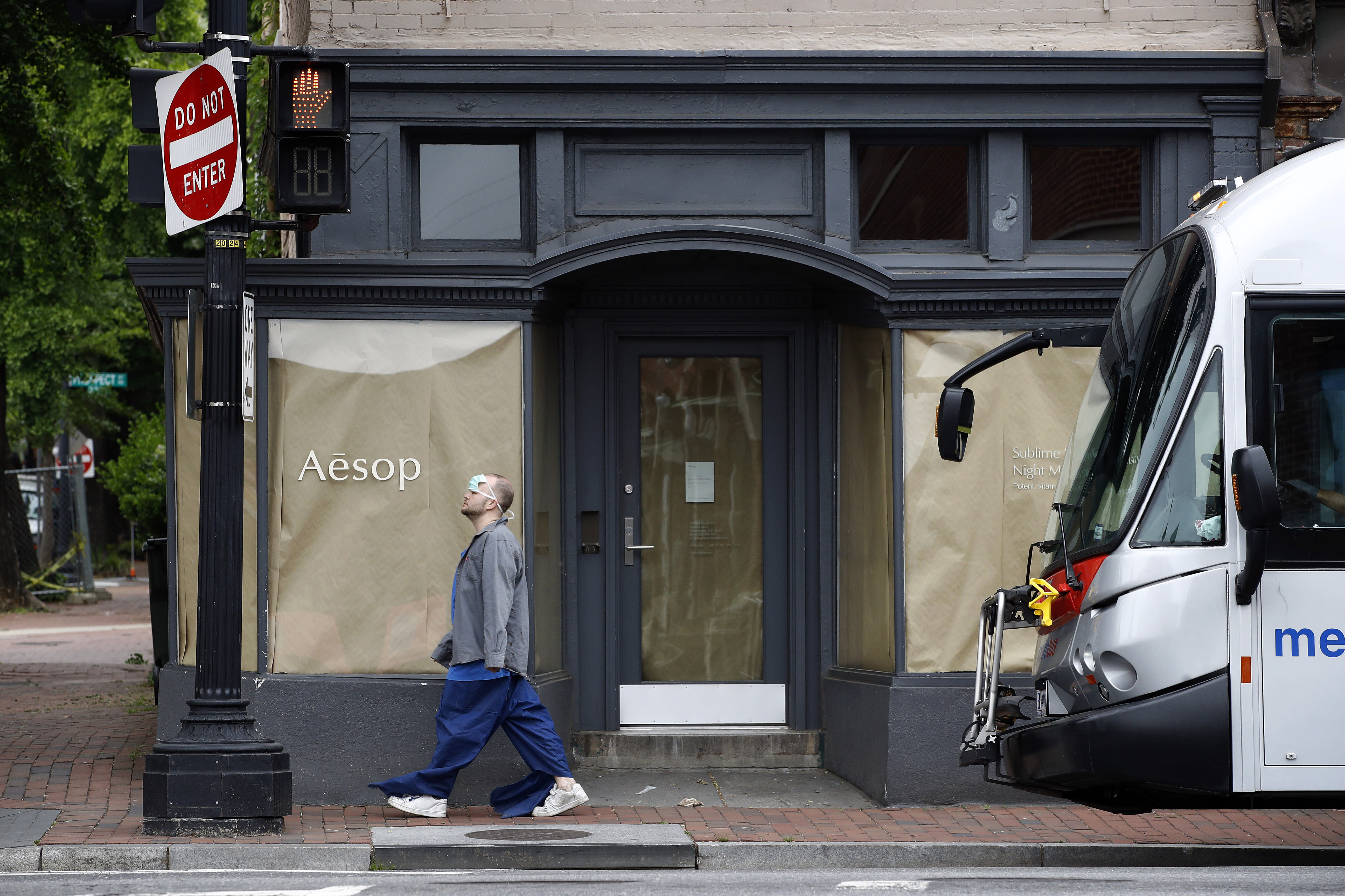 A man wears a face mask to protect against the spread of the new coronavirus on his forehead as he walks past a closed store in the Georgetown neighborhood of Washington, Thursday, May 21, 2020. The District of Columbia is under a stay-home order for all residents in an effort to slow the spread of the new coronavirus. (AP Photo/Patrick Semansky)